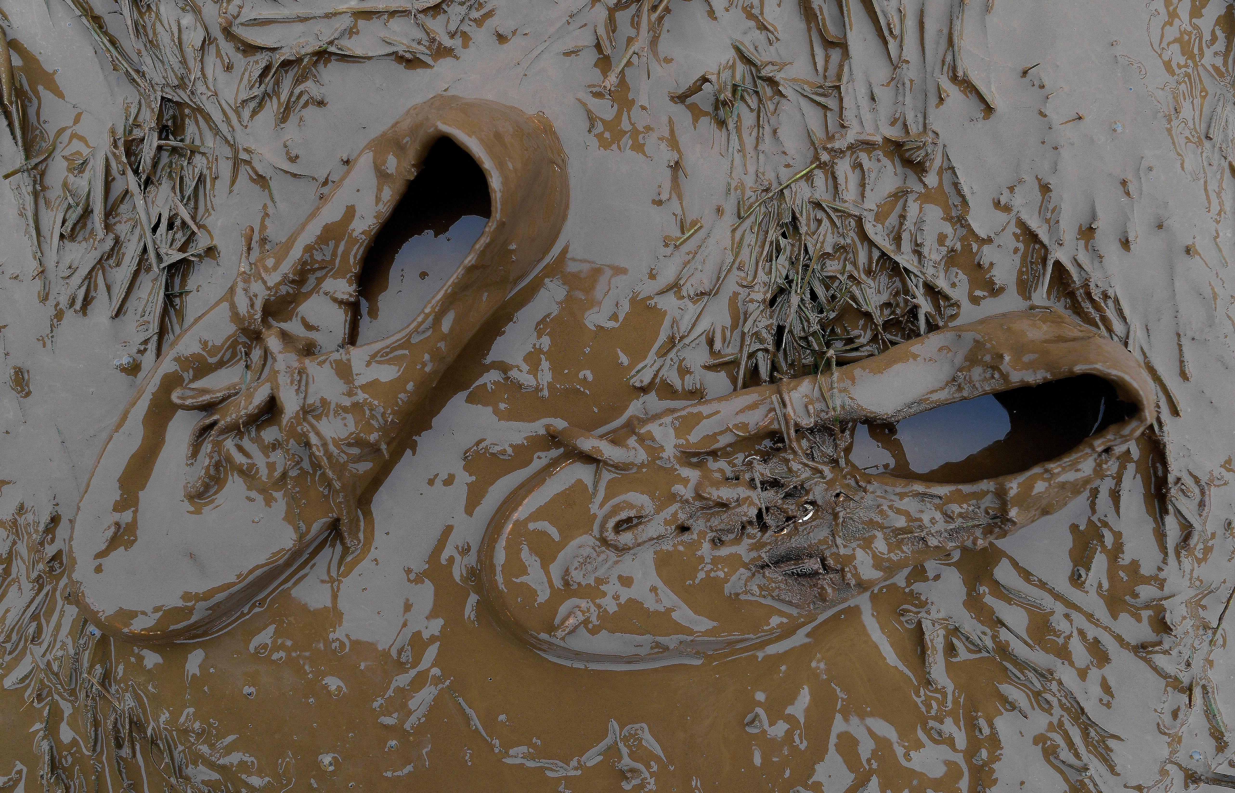 A pair of shoes are left in deep mud in the infield ahead of the 143rd Preakness Stakes horse race at Pimlico race track, Saturday, May 19, 2018, in Baltimore. (AP Photo/Mike Stewart)