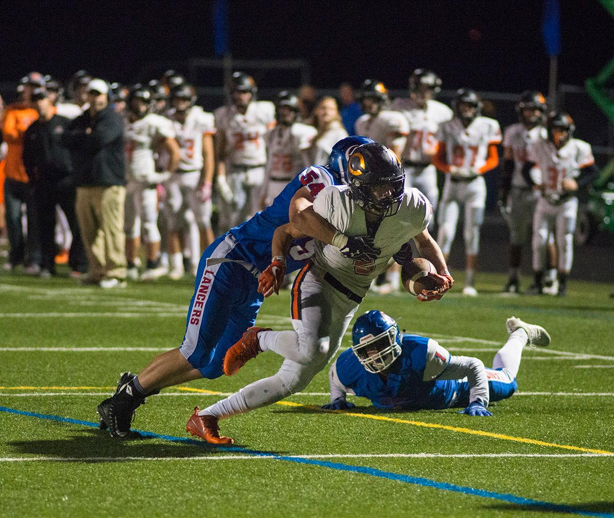 Crater Comets Cade Weaver (#5) attempts to carry the ball past Churchill Lancers defense. Churchill defeated Crater 63-21 on Friday at their homecoming game. Churchill remains undefeated with a conference record of 9-0. Photo by Rhianna Gelhart, Oregon News Lab