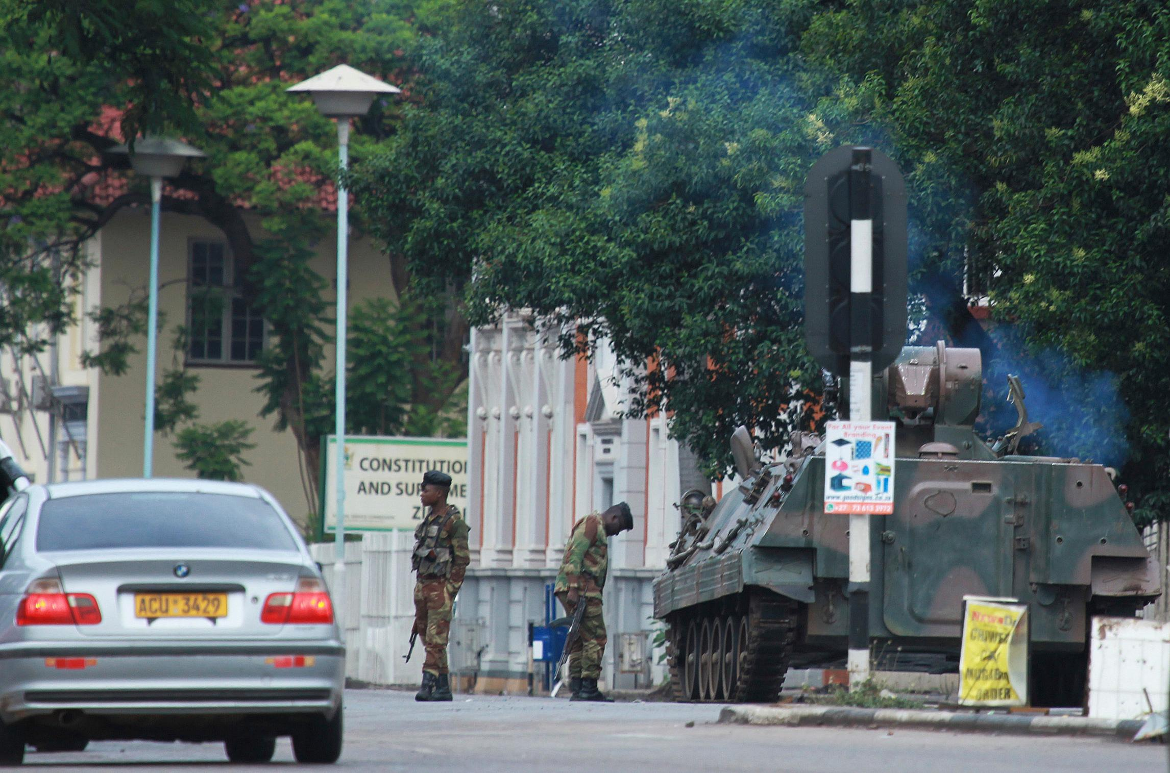 "A military tank is seen with armed soldiers on the road leading to President Robert Mugabes office in Harare, Zimbabwe Wednesday, Nov. 15, 2017. Overnight, at least three explosions were heard in the capital, Harare, and military vehicles were seen in the streets. On Monday, the army commander had threatened to ""step in"" to calm political tensions over the 93-year-old Mugabe's possible successor. (AP Photo/Tsvangirayi Mukwazhi)"