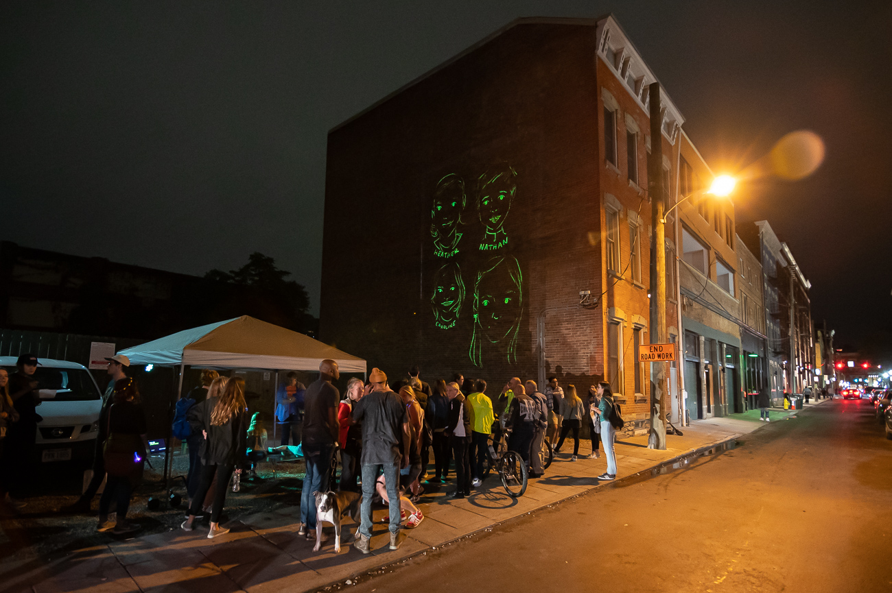 PICTURED NEIGHBORHOOD: Over-the-Rhine / On 14th Street, across from Empower's offices, an artist draws caricatures of people. Those drawings are then projected onto the side of the building next door. / Image: Phil Armstrong // Published: 10.12.19