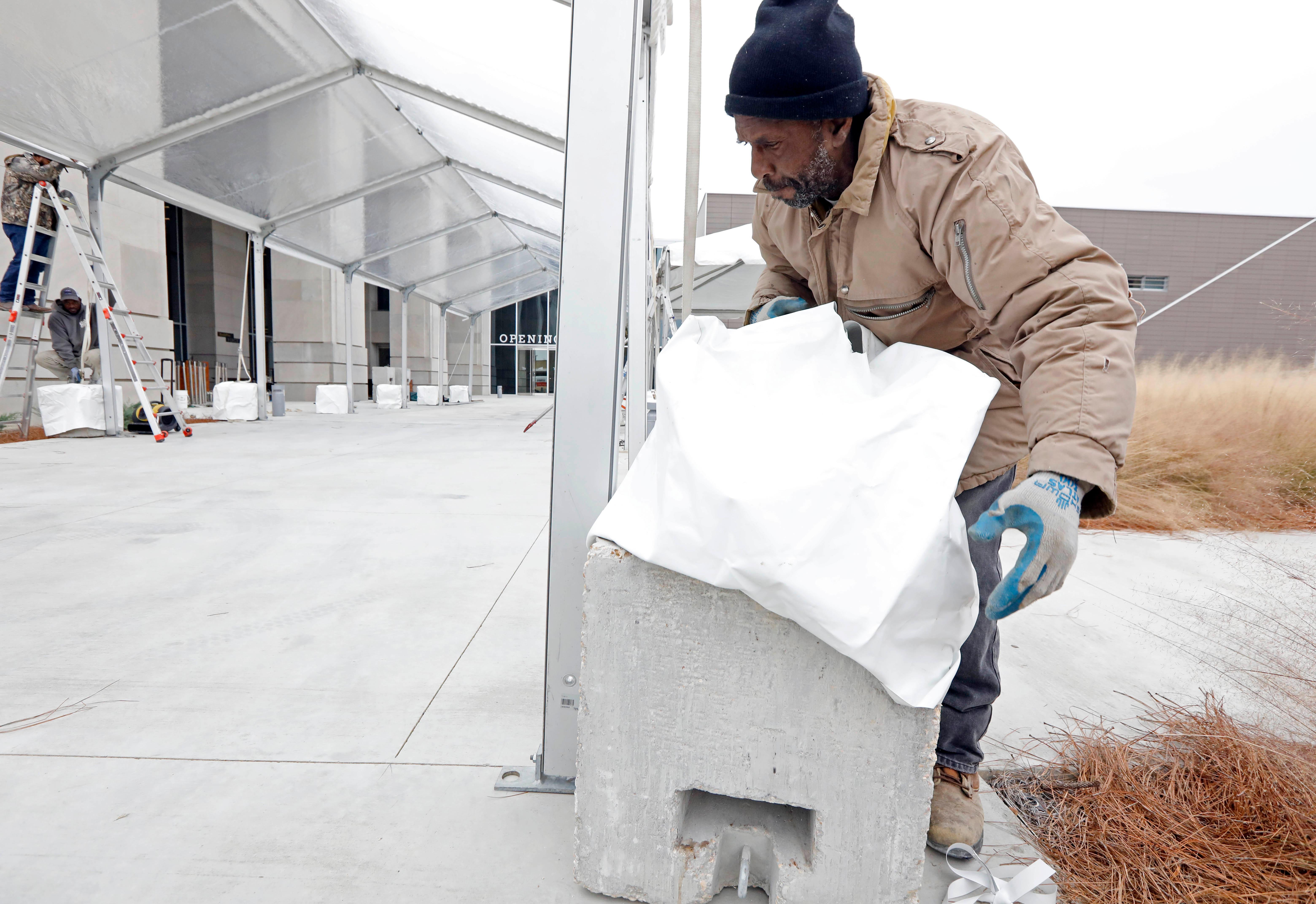 Robert Daugherty, wrestles with a concrete mooring cover as he tries not to step into the muhly grass along the temporary covered walk way to the state's two newest museums, the Museum of Mississippi History and the Mississippi Civil Rights Museum, Thursday, Dec. 7, 2017 in Jackson, Miss. A temporary performance stage, a covered walk way, 2,500 seats are in the process of being built or arranged in the small plaza that rests in front of the two museums. The long-planned Saturday ceremony will mark Mississippi's bicentennial of admission into the union, however the appearance of President Donald Trump at the ceremony has drawn the ire of U.S. Reps. John Lewis, D-Ga., and Bennie Thompson, D-Miss., who announced Thursday they won't attend the opening of Mississippi civil rights and history museums. What was intended as a moment of racial unity and atonement in the state with the largest share of African-Americans is descending into racial and partisan strife after Republican Mississippi Gov. Phil Bryant invited fellow Republican Trump to attend. (AP Photo/Rogelio V. Solis)