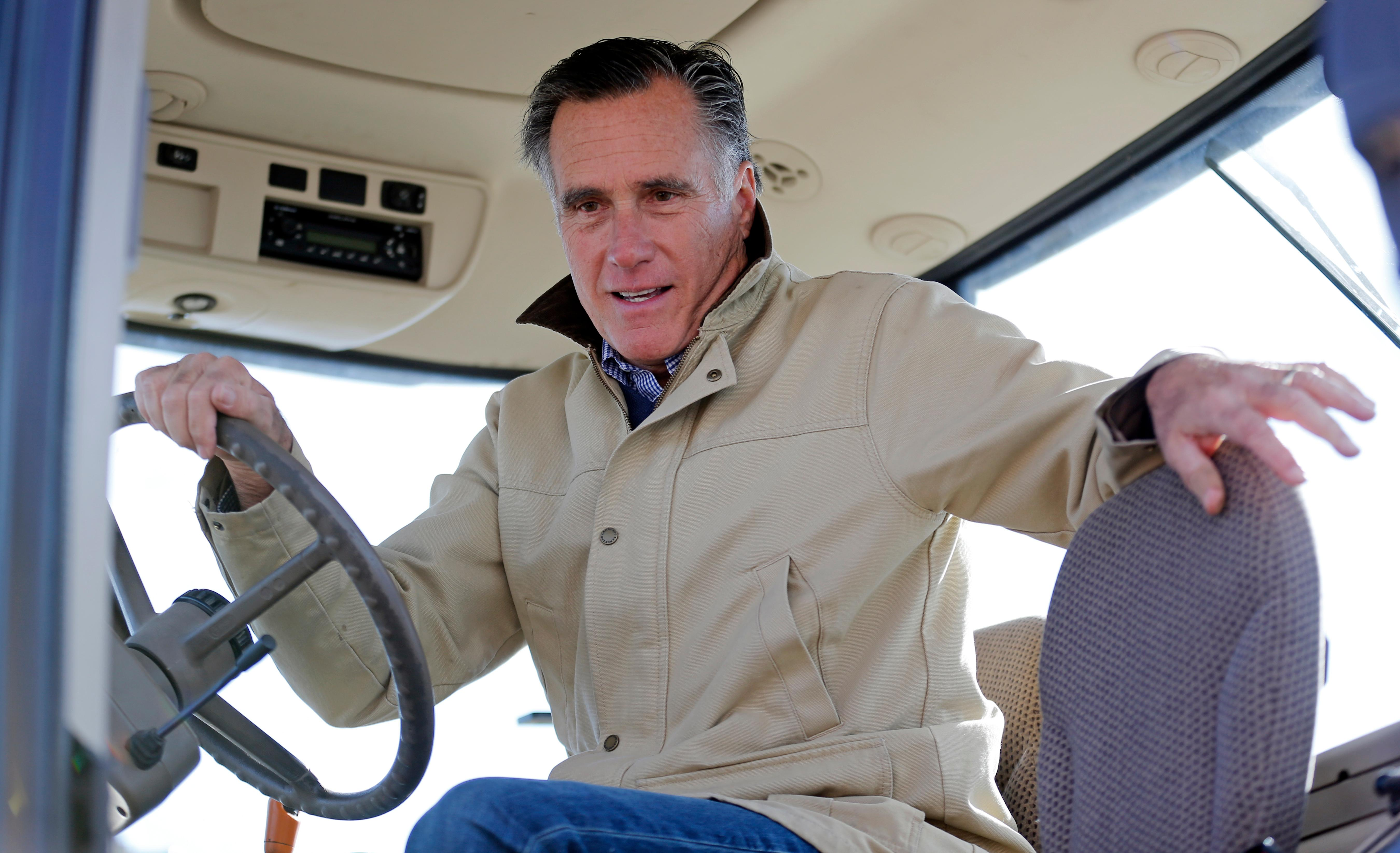 Former Republican presidential candidate Mitt Romney holds the wheel of a tractor during a tour of Gibson's Green Acres Dairy Friday, Feb. 16, 2018, in Ogden, Utah. The 2012 Republican presidential candidate plans to bid for the seat being vacated by retiring seven-term Utah Sen. Orrin Hatch. (AP Photo/Rick Bowmer)