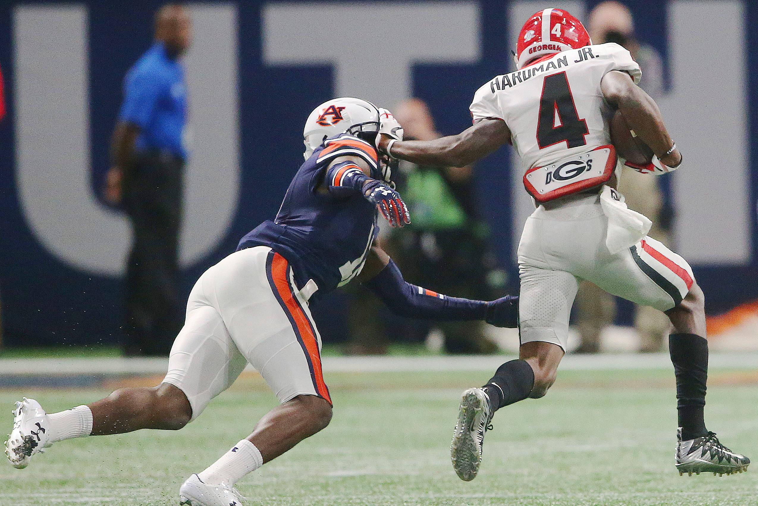 Georgia wide receiver Mecole Hardman (4) hits Auburn defensive back Jamel Dean (12) during the first half of the Southeastern Conference championship NCAA college football game, Saturday, Dec. 2, 2017, in Atlanta. (AP Photo/John Bazemore)