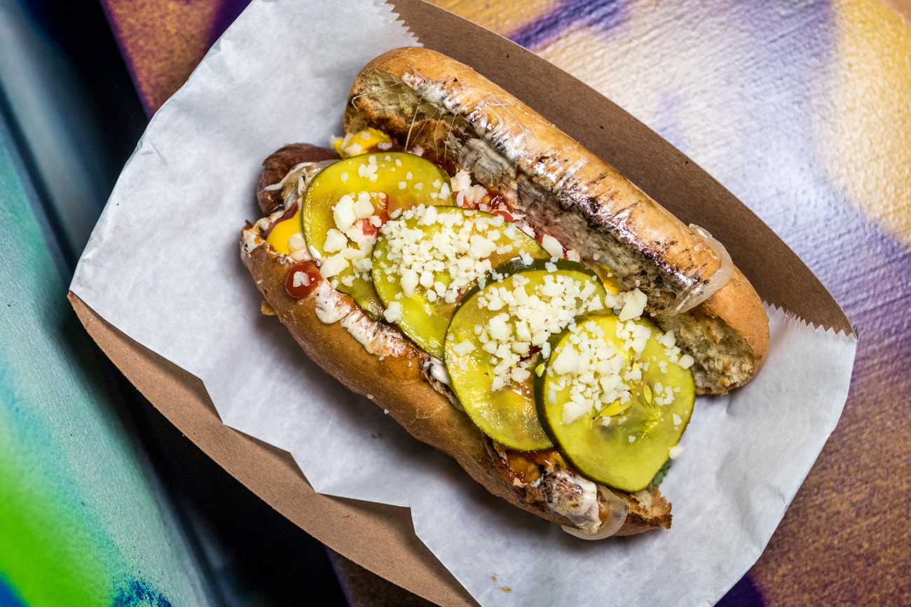 El Tocino Papi Jochos: Papi's all-beef hot dog wrapped in bacon, grilled onions, house-made chili sauce, queso oaxaca, ketchup, mustard, mayo, tomato, house pickles, and cotija / Image: Catherine Viox // Published: 8.24.20