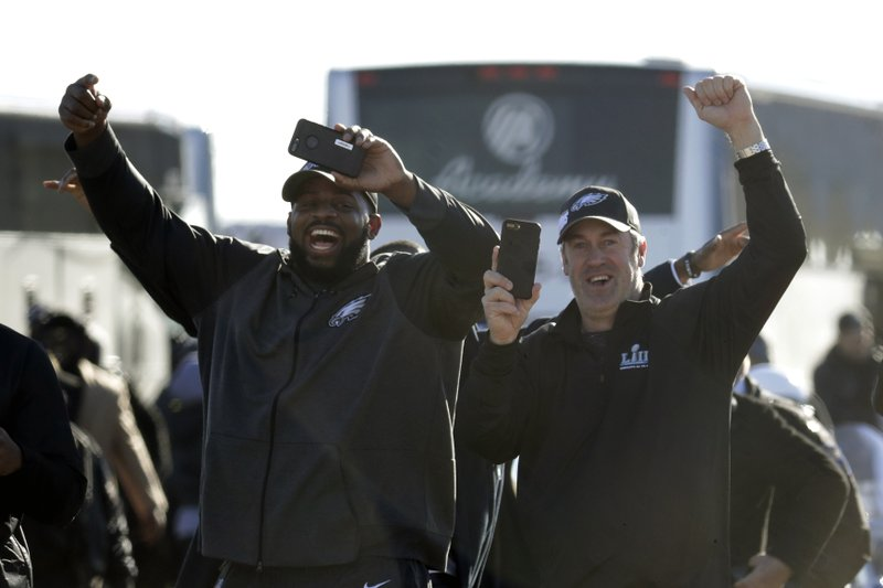 <p>Philadelphia Eagles defensive tackle Fletcher Cox, left, and head coach Doug Pederson approach a fence where fans gathered to welcome the team Monday, Feb. 5, 2018, at Philadelphia International Airport a day after defeating the New England Patriots in Super Bowl 52. (AP Photo/Julio Cortez)</p>