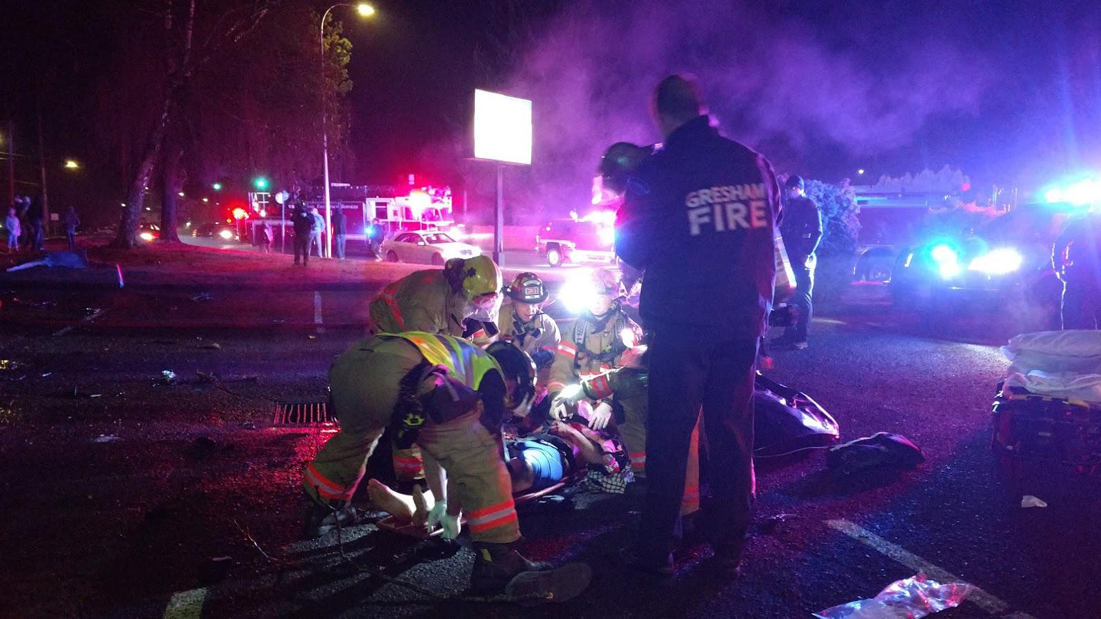 Firefighters and paramedics treat a person injured in a rollover crash near Southeast 182nd Avenue and Yamhill Street on Monday night, Dec. 23, 2019. (Photo: Gresham Fire Department)