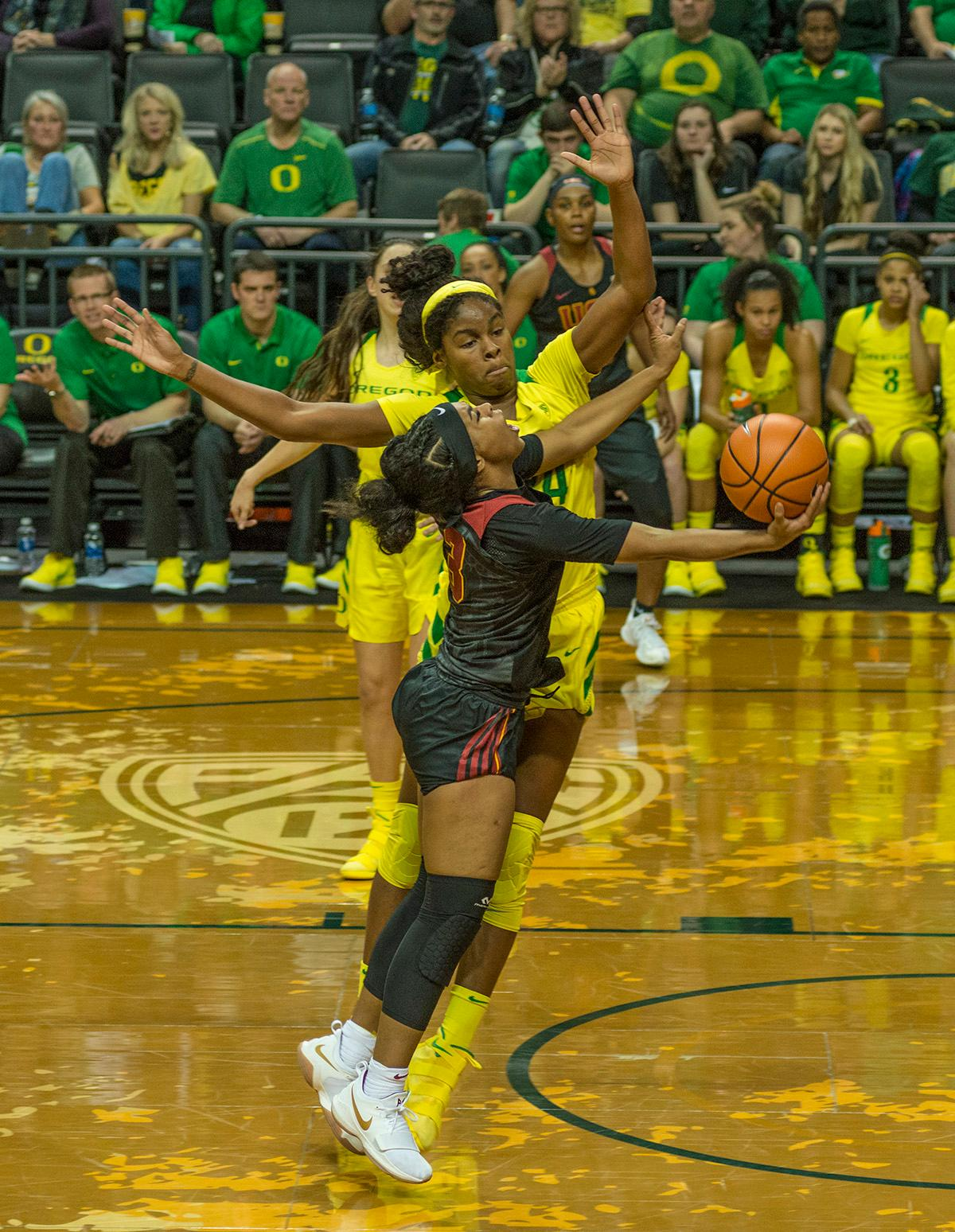 Oregon Ducks Ruthy Hebard (#24, yellow jersey) attempts to block the shot of USC Trojans Minyon Moore (#3). The Oregon Ducks defeated the USC Trojans 80-74 on Friday at Matthew Knight Arena in a game that went into double overtime. Lexi Bando sealed the Ducks' victory by scoring a three-pointer in the closing of the game. Ruthy Hebard set a new NCAA record of 30 consecutive field goals over three games, the old record being 28. Ruthy Hebard got a double-double with 27 points and 10 rebounds, Mallory McGwire also had 10 rebounds. The Ducks had four players in double digits: Ruthy Hebard with 27; Maite Cazorla with 17; Sabrina Ionescu with 15; and Lexi Bando with 11. The Ducks are now 24-4, 13-2 in the Pac-12, and are tied for first with Stanford. Photo by Dan Morrison, Oregon News Lab