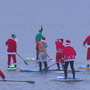 Watch: Paddle boarding Santas skim Lake Washington along I-90 bridge for good cause