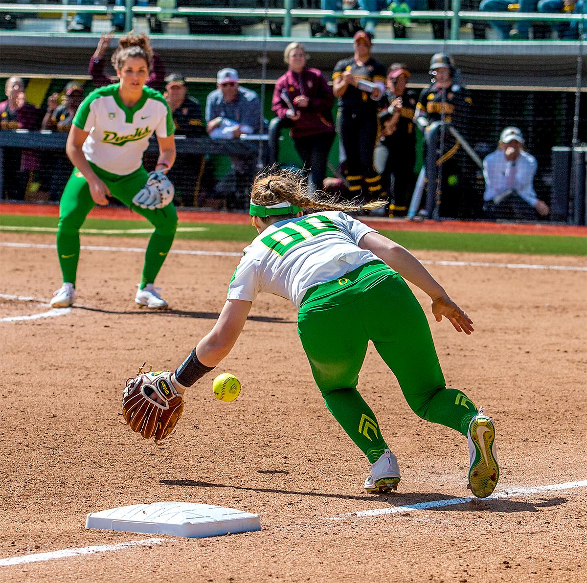 The Duck's Jenna Lilley (#00) goes for the catch before throwing to first base. The Oregon Ducks Softball team took their third win over the Arizona Sun Devils, 1-0, in the final game of the weekends series that saw the game go into an eighth inning before the Duck?s Mia Camuso (#7) scored a hit allowing teammate Haley Cruse (#26) to run into home plate for a point. The Ducks are now 33-0 this season and will next play a double header against Portland State on Tuesday, April 4 at Jane Sanders Stadium. Photo by August Frank, Oregon News Lab