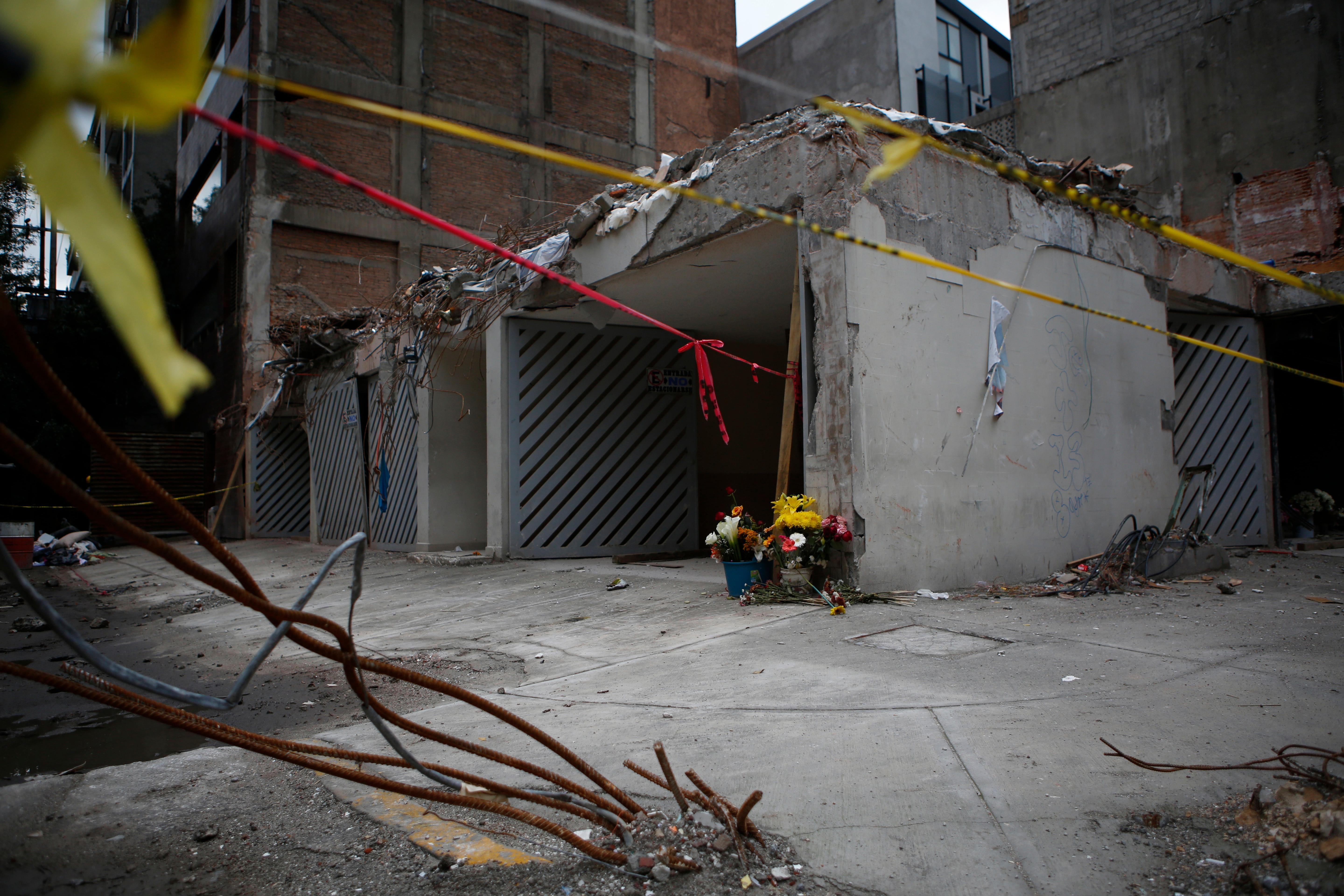 Flowers serve as an informal memorial at what remains of a seven-story apartment building that collapsed at 107 Amsterdam on the corner with Laredo, in the Condesa neighborhood of Mexico City, Friday, Sept. 29, 2017.  (AP Photo/Rebecca Blackwell)
