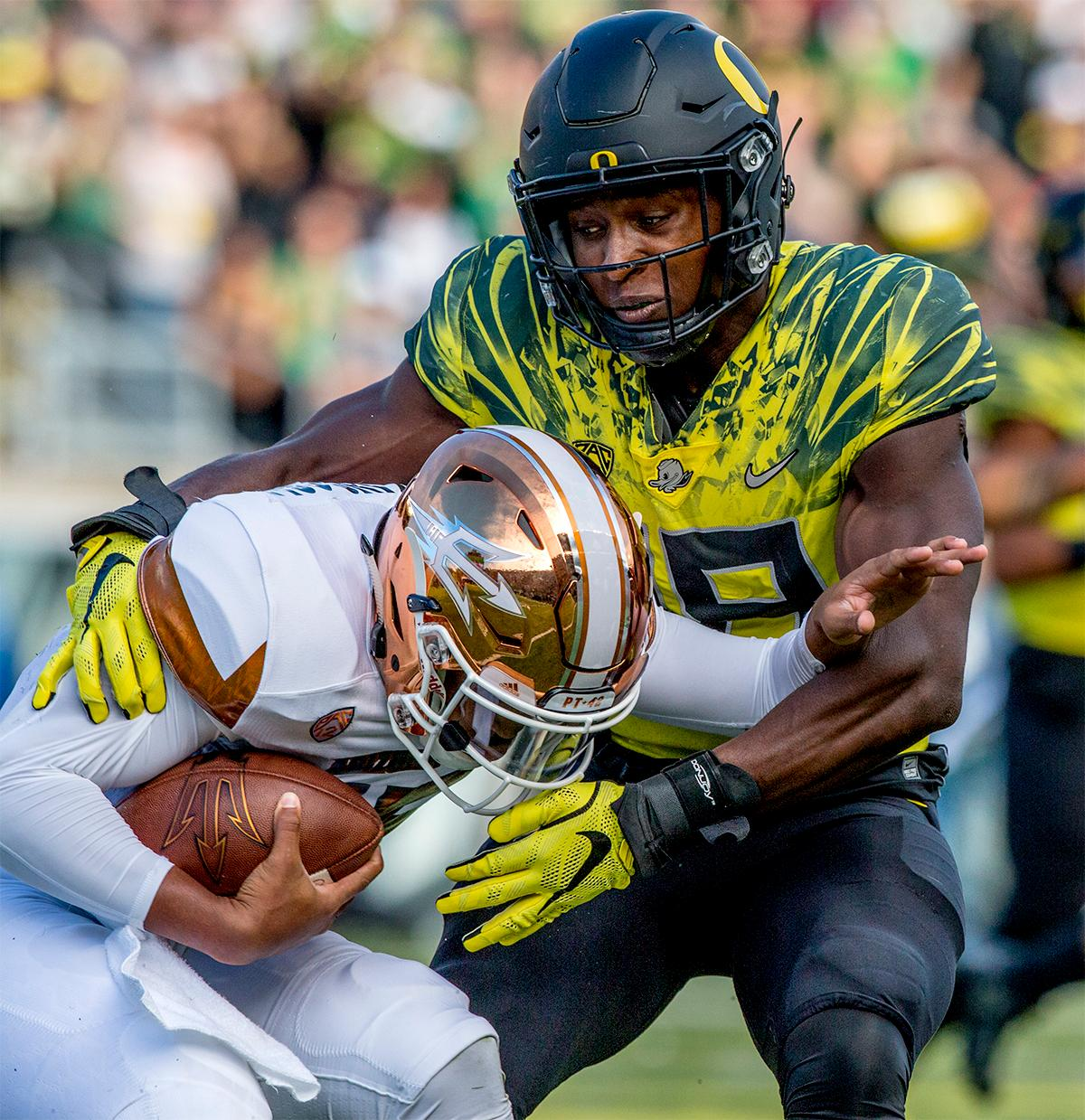 The Sun Devils' Bryson Echols (#15) is brought down by the Ducks. The Oregon Ducks broke their losing streak by defeating the ASU Sun Devils on Saturday 54-35. Photo by August Frank, Oregon News Lab