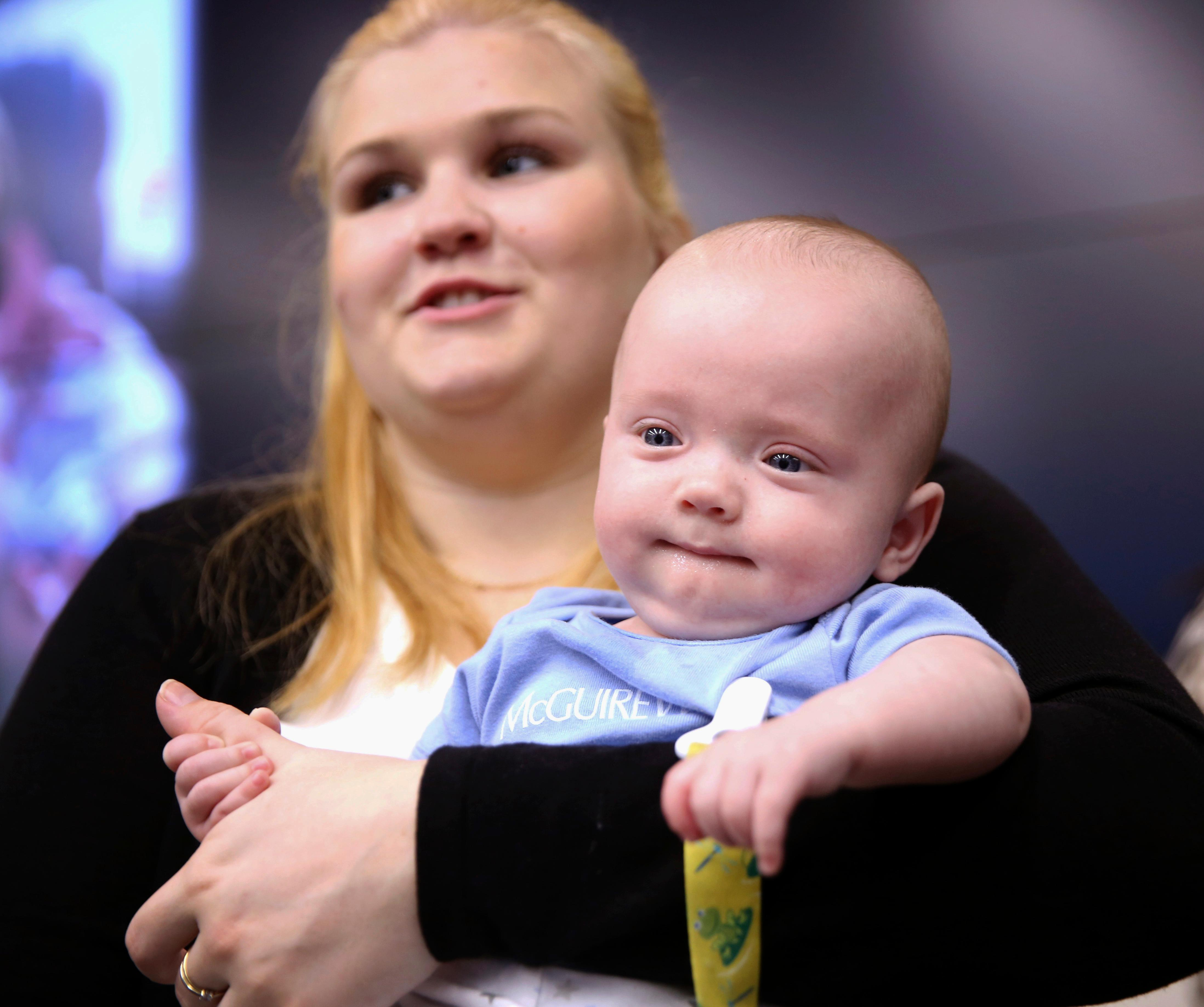 "Baudinet family friend Jennifer Bolin holds Luke Thomas Baudinet while the quintuplets' family is greeted at McGuireWoods on Tuesday May 16, 2017 in Richmond, Va. The Baudinet quintuplets made their public debut Tuesday in Richmond. Ava Louise, Clara Catherine, Camille ""Millie"" Whitney, Luke Thomas, and Isabelle Frances were born Dec. 4 in Arizona.   (Shelby Lum/Richmond Times-Dispatch via AP)"