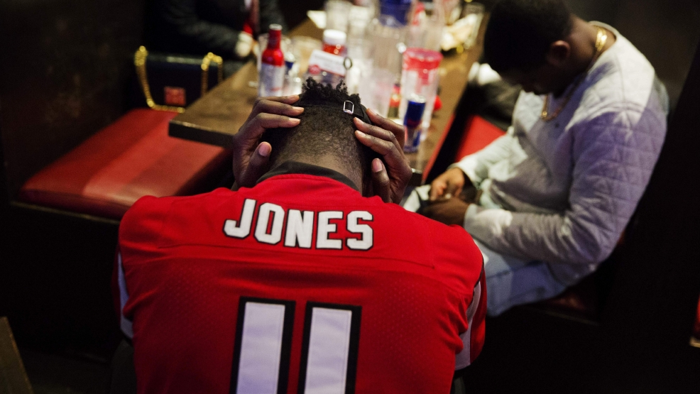 Atlanta Falcons fan CJ Scott hangs his head in his hands at Taco Mac restaurant in Atlanta after watching on television the New England Patriots beat Atlanta in Super Bowl 51 Sunday in Houston. The Patriots won 34-28 in overtime. THE ASSOCIATED PRESS