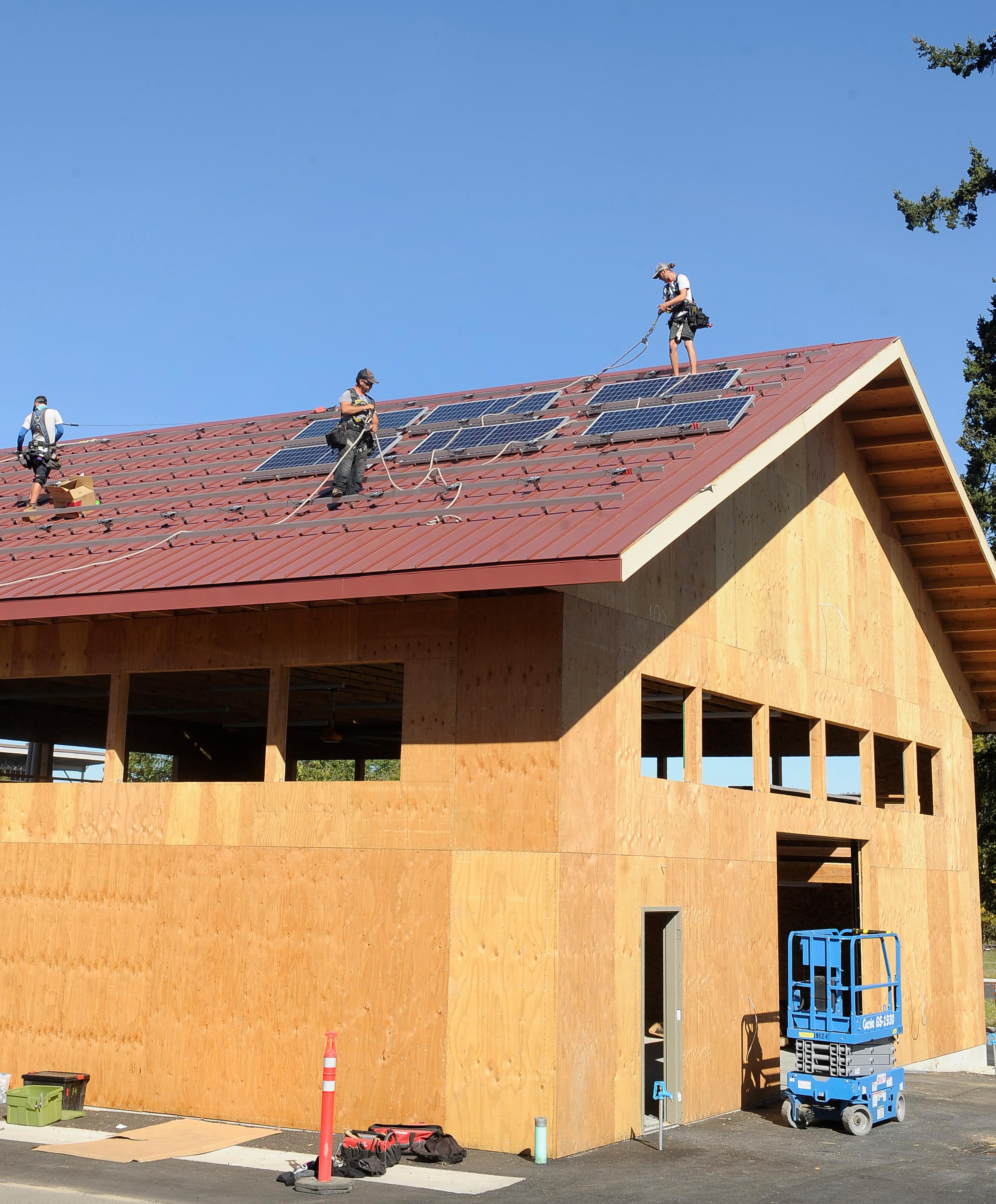 Andy Atkinson / Mail Tribune A team from True South Solar begin installing solar panels on top of the new SOU rec centers storage building Tuesday morning.