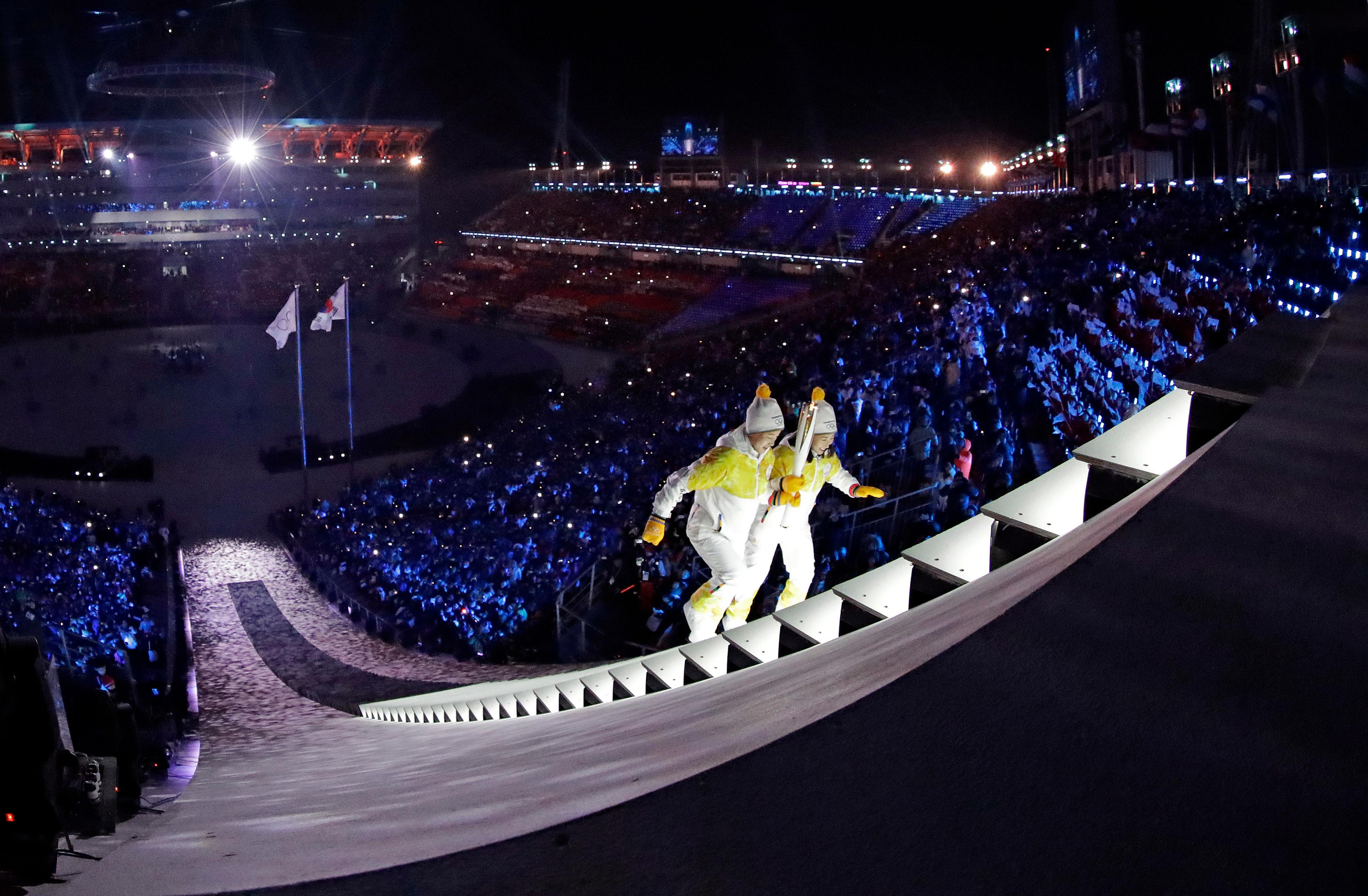 North Korea's Jong Su Hyon, left, and South Korea's Park Jong-ah carry the torch during the opening ceremony of the 2018 Winter Olympics in Pyeongchang, South Korea, Friday, Feb. 9, 2018. (AP Photo/David J. Phillip,Pool)