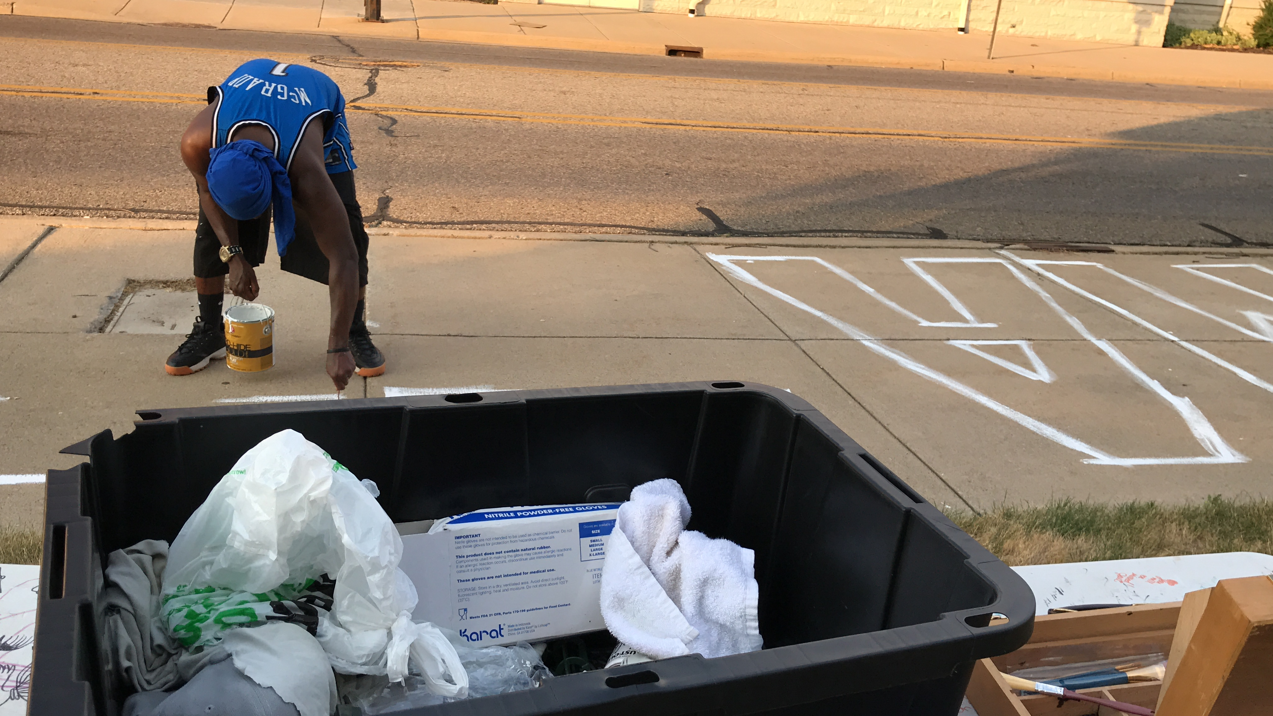 Gerald King of Battle Creek works on the letter T in the word matter, as several of his supplies await nearby for the next portion of the sidewalk mural project in Battle Creek, Michigan, on Tuesday, July 7, 2020. (WWMT/Jason Heeres)