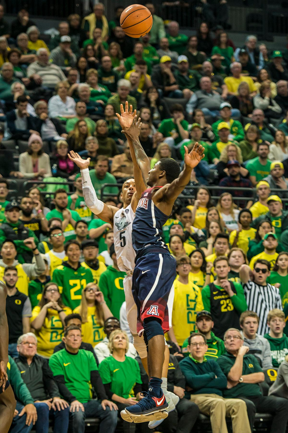 Oregon's Elijah Brown shoots for three over an Arizona defender in theor matchup at Matthew Knight Arena Saturday. The Ducks upset the fourteenth ranked Wildcats 98-93 in a stunning overtime win in front of a packed house of over 12,000 fans for their final home game to improve to a 19-10 (9-7 PAC-12) record on the season. Oregon will finish out regular season play on the road in Washington next week against Washington State on Thursday, then Washington on the following Saturday. (Photo by Colin Houck)