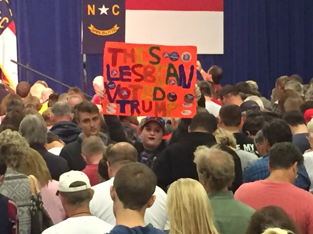 "Trump rally attendee holds a sign reading ""THIS LESBIAN VOTED TRUMP."" (Photo credit: WLOS staff)"