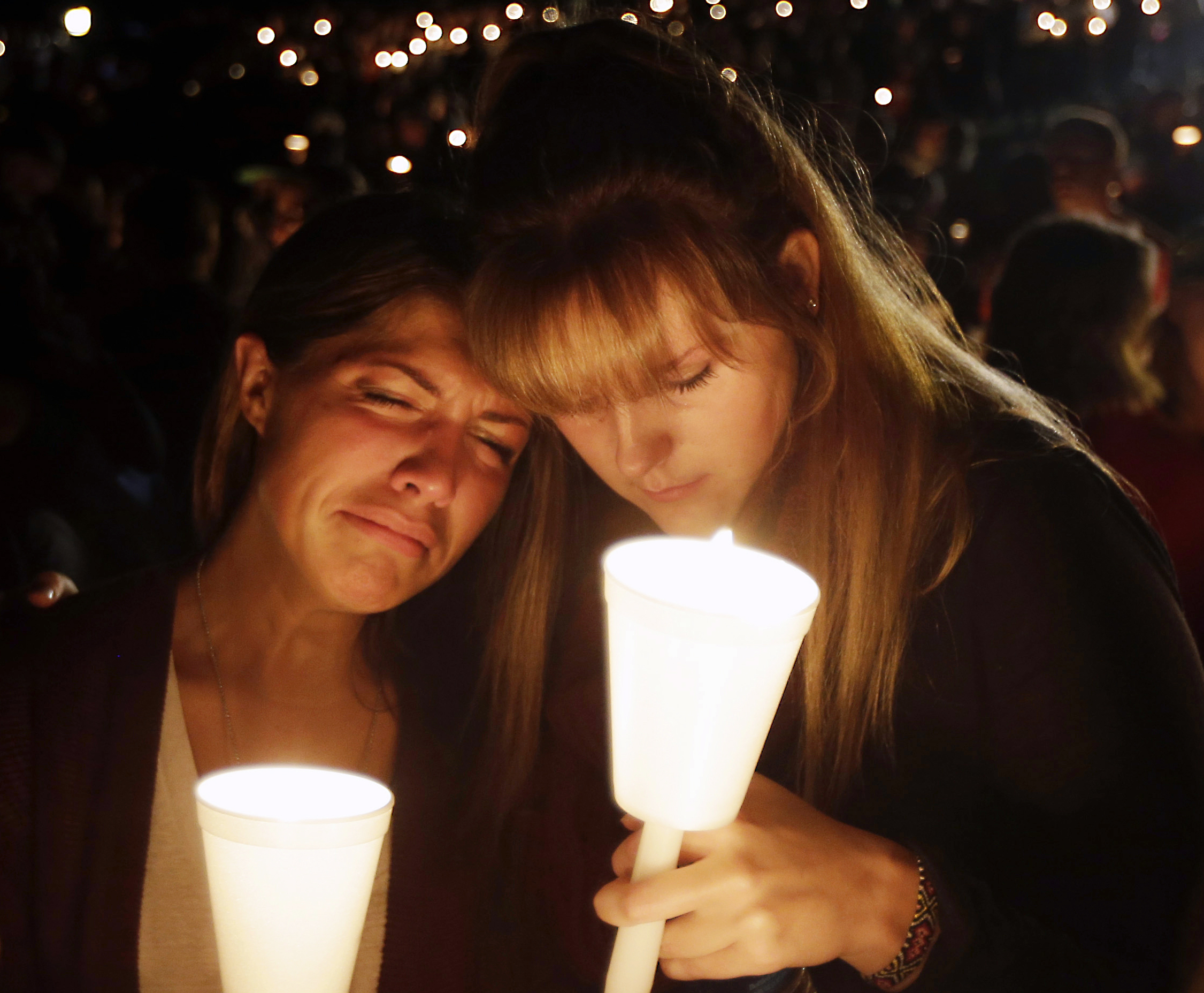 Kristen Sterner, left, and Carrissa Welding, both students at Umpqua Community College, embrace each other during a candlelight vigil for those killed during a shooting at the college, Thursday, Oct. 1, 2015, in Roseburg, Ore. (AP Photo/Rich Pedroncelli)