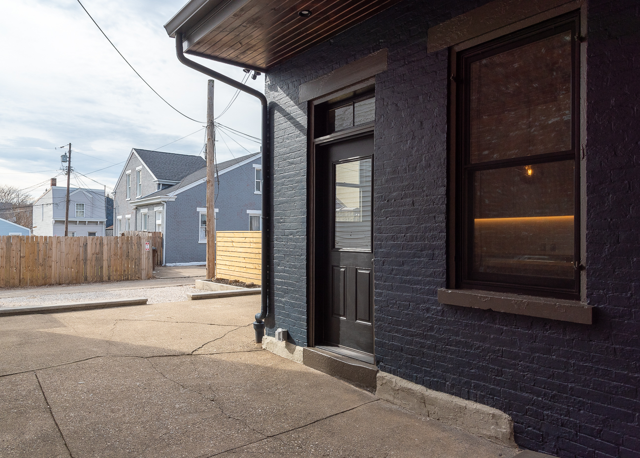 Just beyond the breezeway, the property opens up to a modest patio with a two-car parking area behind the house. / Image: Phil Armstrong, Cincinnati Refined // Published: 3.15.19