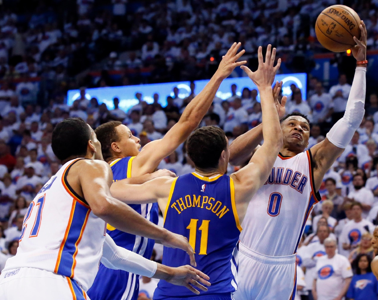 Oklahoma City Thunder guard Russell Westbrook (0) goes after a loose ball against Golden State Warriors guard Stephen Curry (30) and guard Klay Thompson (11) as guard Andre Roberson (21) looks on during the second half in Game 4 of the NBA basketball Western Conference finals in Oklahoma City, Tuesday, May 24, 2016. (AP Photo/Sue Ogrocki)