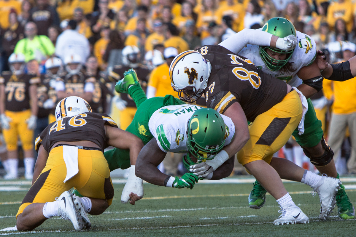 Oregon running back Royce Freeman (#21) dives through Wyoming defenders Cassh Maluia (#46) and Conner Cain (#87). The Oregon Ducks lead the Wyoming Cowboys 42 to 10 at the end of the first half on Saturday, September 16, 2017 in Laramie, Wyo. Photo by Austin Hicks, Oregon News Lab