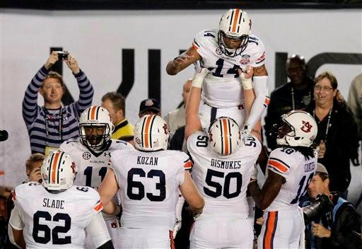 Auburn quarterback Nick Marshall is lifted by teammates after rushing for a touchdown during the first half of the NCAA BCS National Championship college football game against Florida State Monday, Jan. 6, 2014, in Pasadena, Calif.