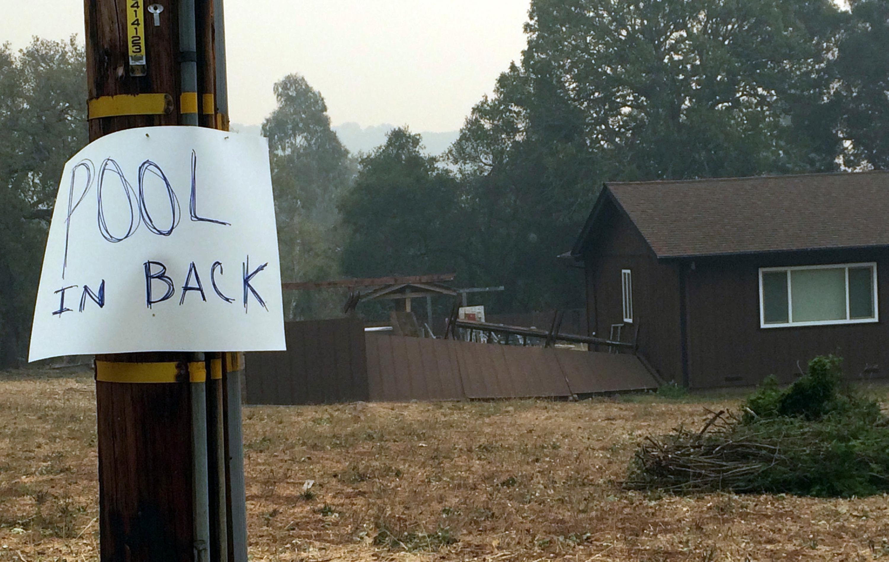 A residence in the hills above Sonoma, Calif., has a posted sign alerting people to an available pool if needed to shelter from wildfires Friday, Oct. 13, 2017. Stories of some people who lived through the inferno by standing in backyard swimming pools this week is spreading. (AP Photo/Ellen Knickmeyer)