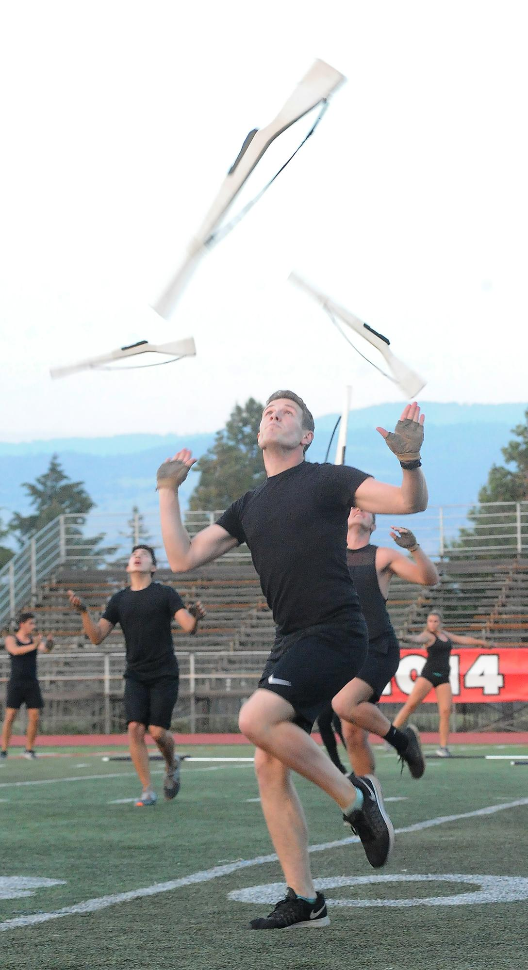 Dancers toss prop rifles into the air during a performance of the Santa Clara Vanguard Drum and Bugle Corps. Photo by Denise Baratta