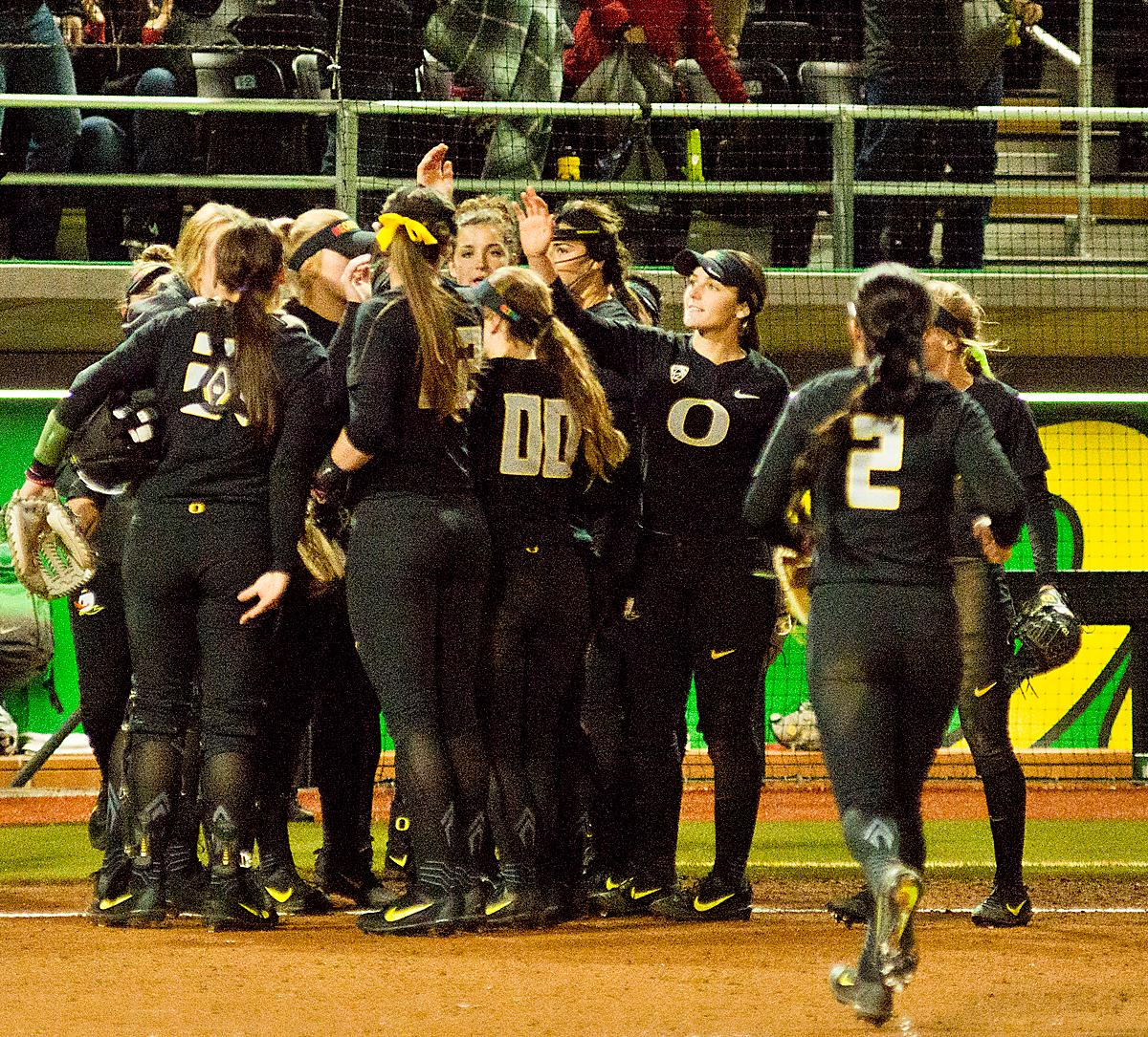 The Ducks celebrate their win over the Huskies. In Game Two of a three-game series, the University of Oregon Ducks softball team defeated the University of Washington Huskies 4-1 Friday night in Jane Sanders Stadium. Danica Mercado (#2), Alexis Mack (#10) and Mia Camuso (#7) all scored in the win, Mack twice. The Ducks play the Huskies for the tie breaker on Saturday with the first pitch at noon. Photo by Dan Morrison, Oregon News Lab