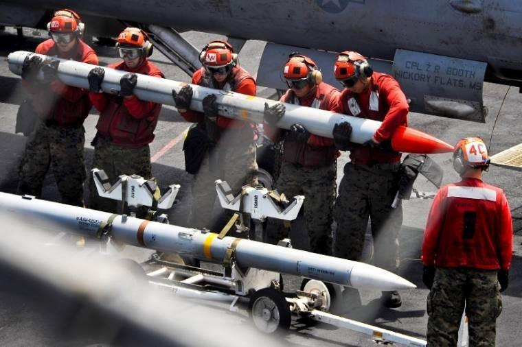 U.S. sailors lift a missile on the flight deck of the aircraft carrier USS Nimitz in the U.S. 5th Fleet area of responsibility, Aug. 31, 2013. The sailors, ordnancemen, are assigned to Marine Fighter Attack Squadron 323.
