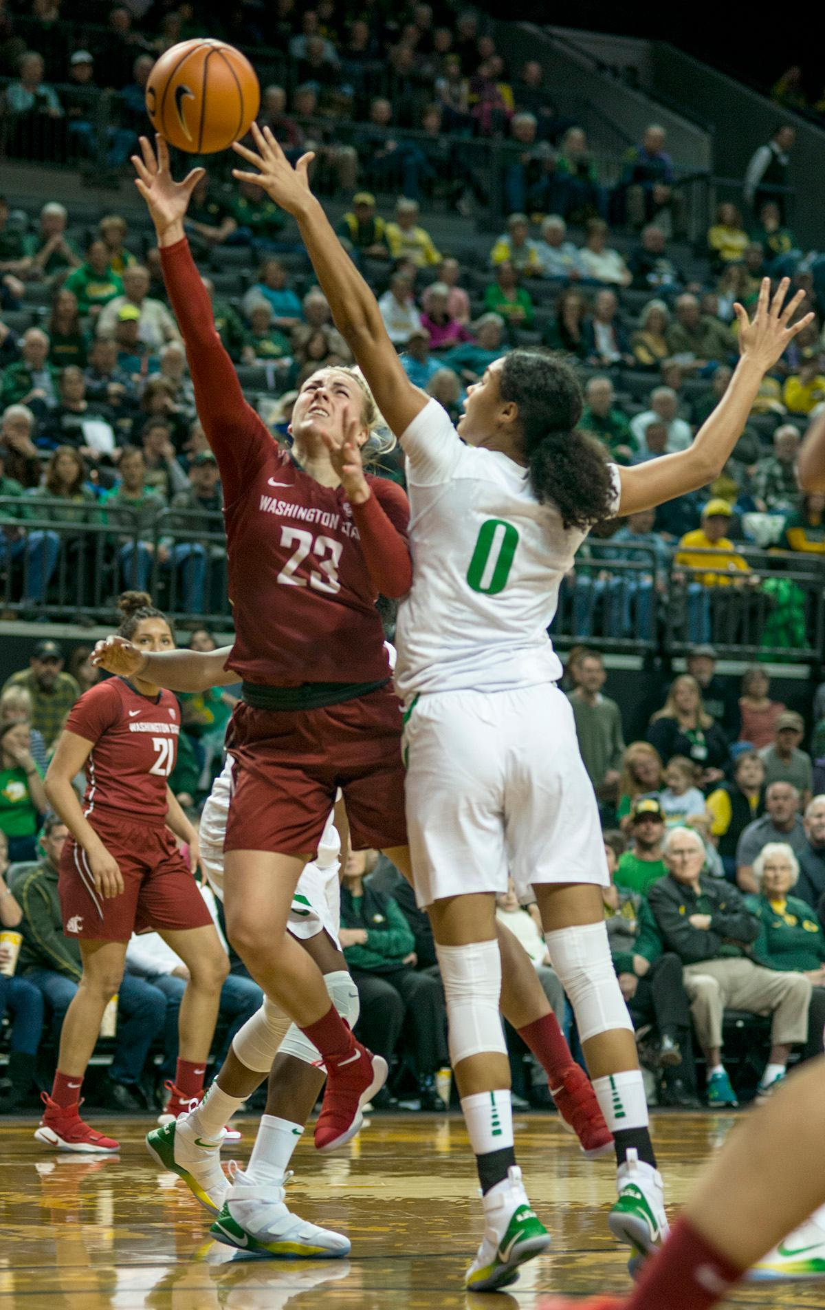 Oregon Ducks Satou Sabally (#0) and Washington State University Cougars Alexys Swedlund (#23) fight for control of a rebound. In their first conference basketball game of the season, the Oregon Women Ducks defeated the Washington State Cougars 89-56 in Matt Knight Arena Saturday afternoon. Oregon's Ruthy Hebard ran up 25 points with 10 rebounds. Sabrina Ionescu shot 25 points with five three-pointers and three rebounds. Lexi Bando added 18 points, with four three-pointers and pulled down three rebounds. Satou Sabally ended the game with 14 points with one three-pointer and two rebounds. The Ducks are now 12-2 overall with 1-0 in conference and the Cougars stand at 7-6 overall and 0-1 in conference play. The Oregon Women Ducks next play the University of Washington Huskies at 1:00 pm on Sunday. Photo by Rhianna Gelhart, Oregon News Lab