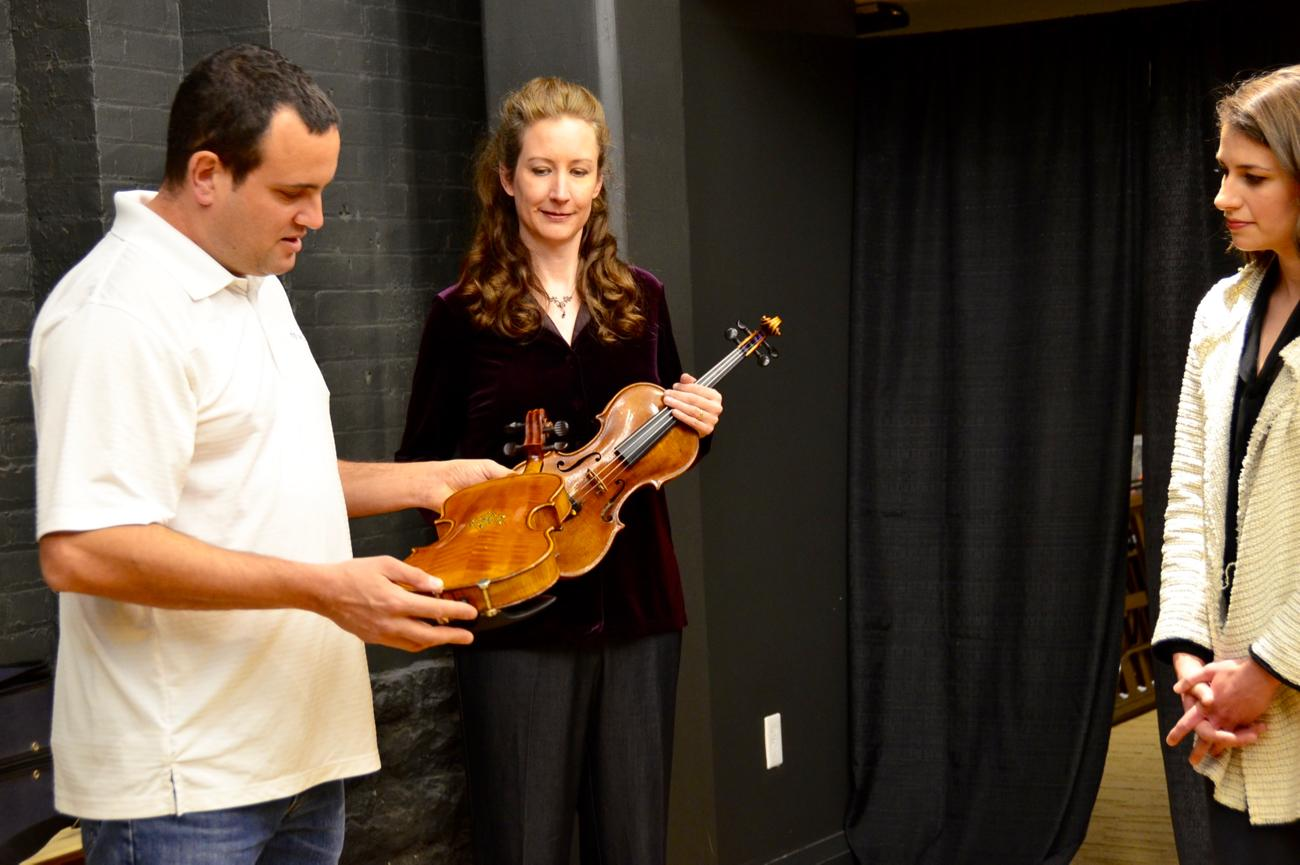 Avshalom Weinstein handing off violins that were saved from the Holocaust to members of the Cincinnati Symphony Orchestra in preparation for the Violins of Hope concert, which will take place on Tuesday, January 23 at Music Hall. / Image: Leah Zipperstein, Cincinnati Refined // Published: 1.21.18<br><p></p>