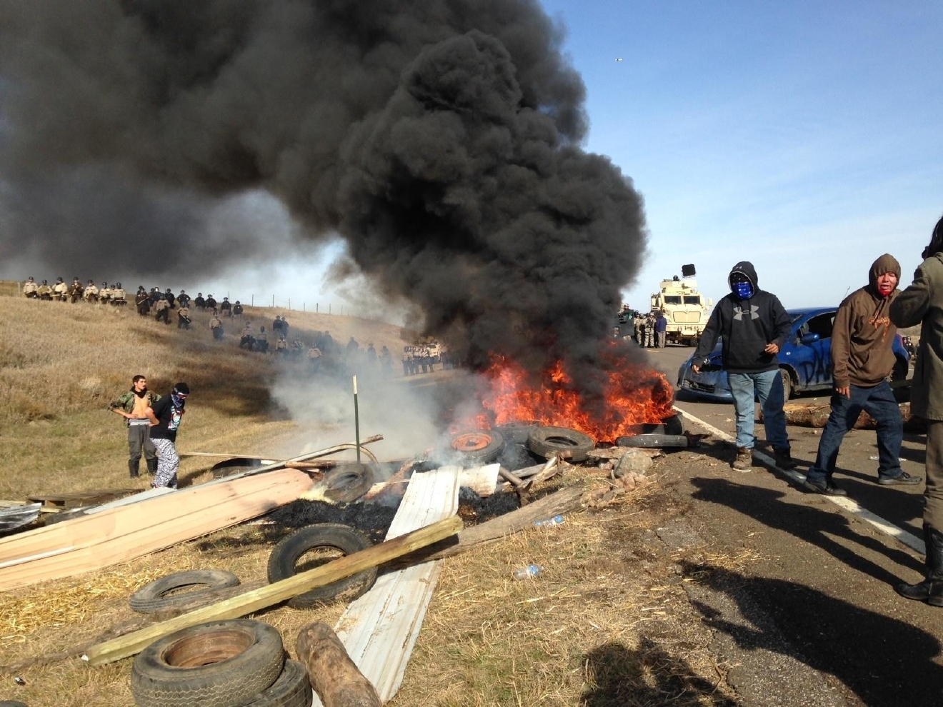 Dakota Access oil pipeline protesters burn debris as officers close in to force them from a camp on private land in the path of pipeline construction, Thursday, Oct. 27, 2016 near Cannon Ball, N.D. Soldiers and law enforcement officers dressed in riot gear began arresting protesters who had set up a camp on private land to block construction of the Dakota Access oil pipeline. (AP Photo/James MacPherson)