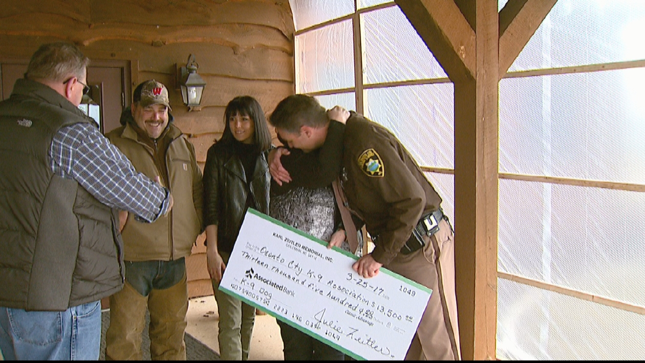 Karl Zeitler Memorial Inc, a local charity, presents the Oconto County Sheriff's Office with a check to purchase a new patrol dog, March 25, 2017. (WLUK)