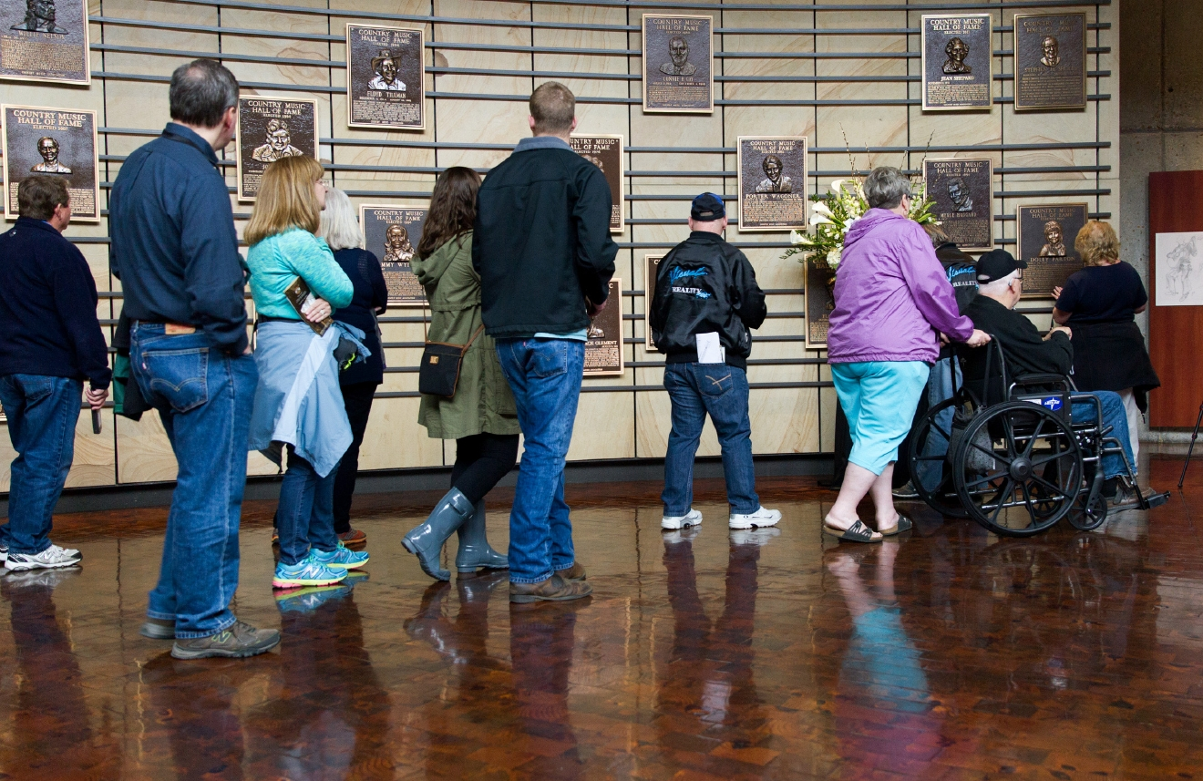 "Visitors wait to pay their condolences at the plaque of Merle Haggard at the Country Music Hall of Fame in Nashville, Tenn., on Wednesday, April 6, 2016. Haggard, who rose from poverty and prison to international fame through his songs about outlaws, underdogs and an abiding sense of national pride in such hits as ""Okie From Muskogee"" and ""Sing Me Back Home,"" died Wednesday at 79, on his birthday. (AP Photo/Erik Schelzig)"