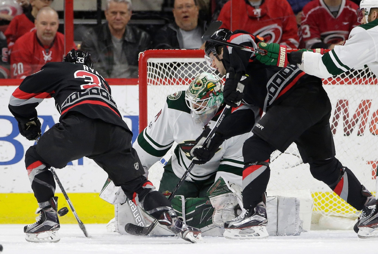 Carolina Hurricanes' Derek Ryan (33) and Lee Stempniak, right, try to score against Minnesota Wild goalie Devan Dubnyk during the first period of an NHL hockey game in Raleigh, N.C., Thursday, March 16, 2017. Ryan scored on the play. (AP Photo/Gerry Broome)