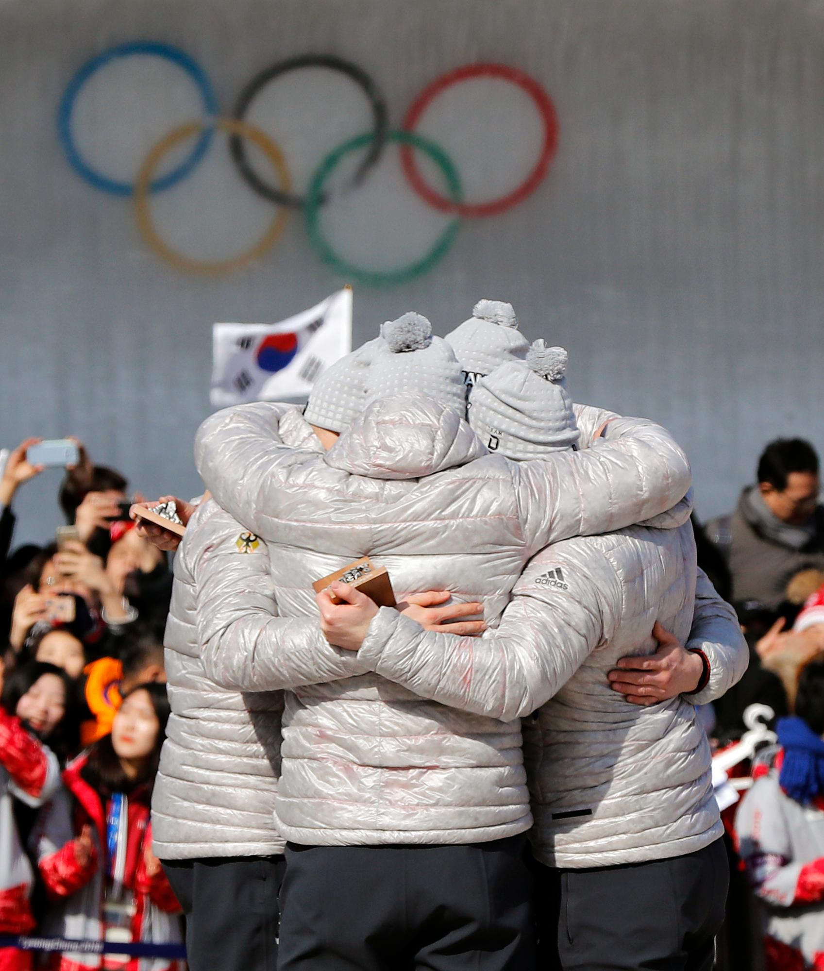 Driver Francesco Friedrich, Candy Bauer, Martin Grothkopp and Thorsten Margis of Germany celebrate after receiving the gold medal during the four-man bobsled competition final at the 2018 Winter Olympics in Pyeongchang, South Korea, Sunday, Feb. 25, 2018. (AP Photo/Andy Wong)