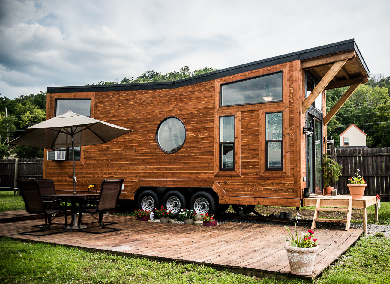 "You can stay at this adorable tiny home stationed at the Riverside Marina in Dayton, KY for $89/night. Originally built in Milford by WheelLife Homes, the 27-foot-long, 240-square-foot tiny home currently serves as a modestly priced Airbnb at the river's edge. Described as the ""Taj Mahal of tiny houses,"" the Airbnb features an attractive industrial aesthetic alongside a list of amenities (such as HVAC and sewer) to make it a comfortable place to stay for the weekend. / Image courtesy of Natalie Gregory // Published: 9.3.19"