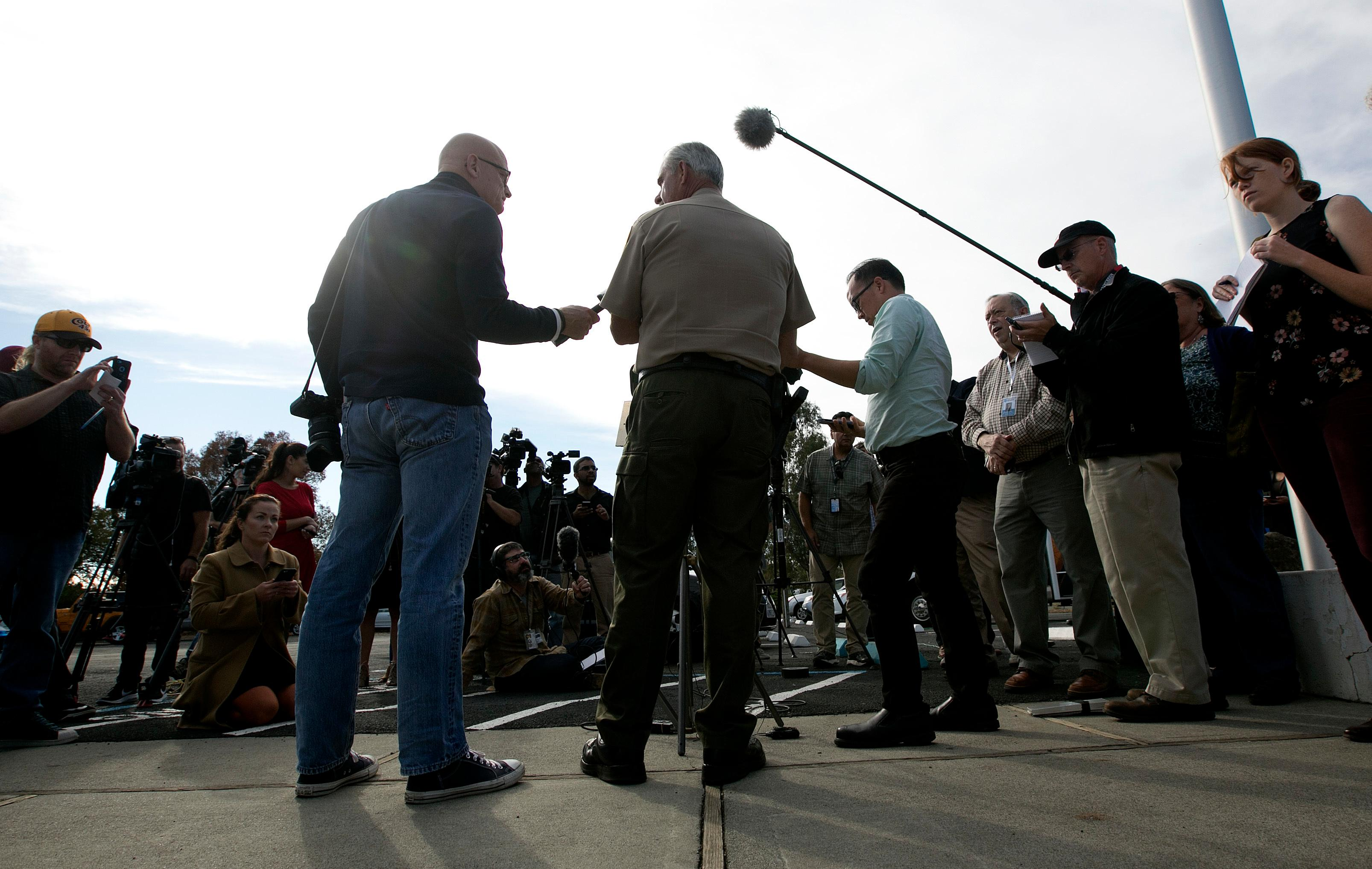 Phil Johnston, center, the assistant sheriff for Tehama County, briefs reporters on the shootings near the Rancho Tehama Elementary School, Tuesday, Nov. 14, 2017, in Corning, Calif. Law enforcement says that five people, including the shooter were killed, and several people including some children were injured and taken to area hospitals. (AP Photo/Rich Pedroncelli)