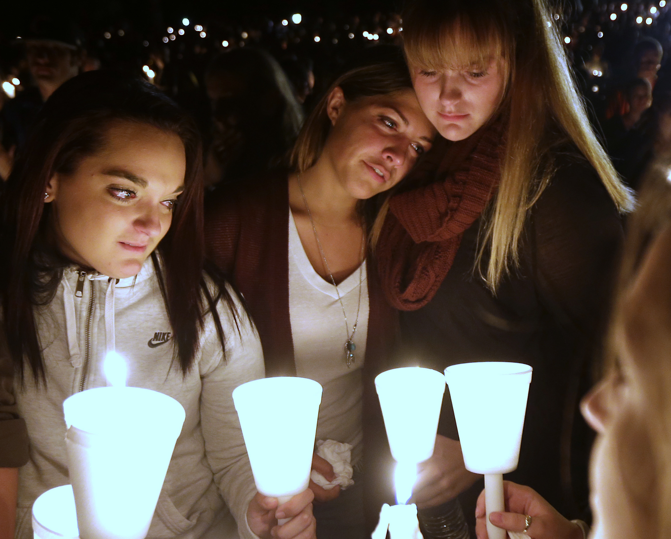 Umpqua Community College students Nicole Zamarripa, left, Kristen Sterner, center and Carrissa Welding, right, join others at Stewart Park, in Roseburg, Ore., for a candlelight vigil for those killed during a fatal shooting at the school Thursday, Oct. 1, 2015. (AP Photo/Rich Pedroncelli)