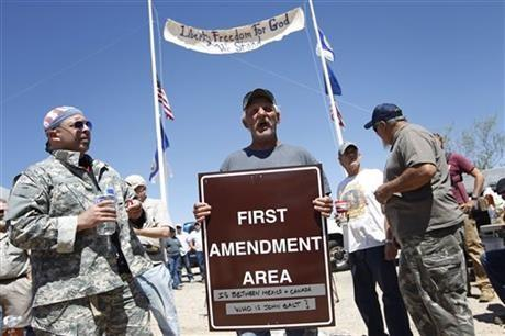 "Charlie Brown holds up a sign from the Bureau of Land Management's ""first amendment area"" during a protest of the Bureau of Land Management's roundup of cattle near Bunkerville, Nev. Thursday, April 10, 2014."