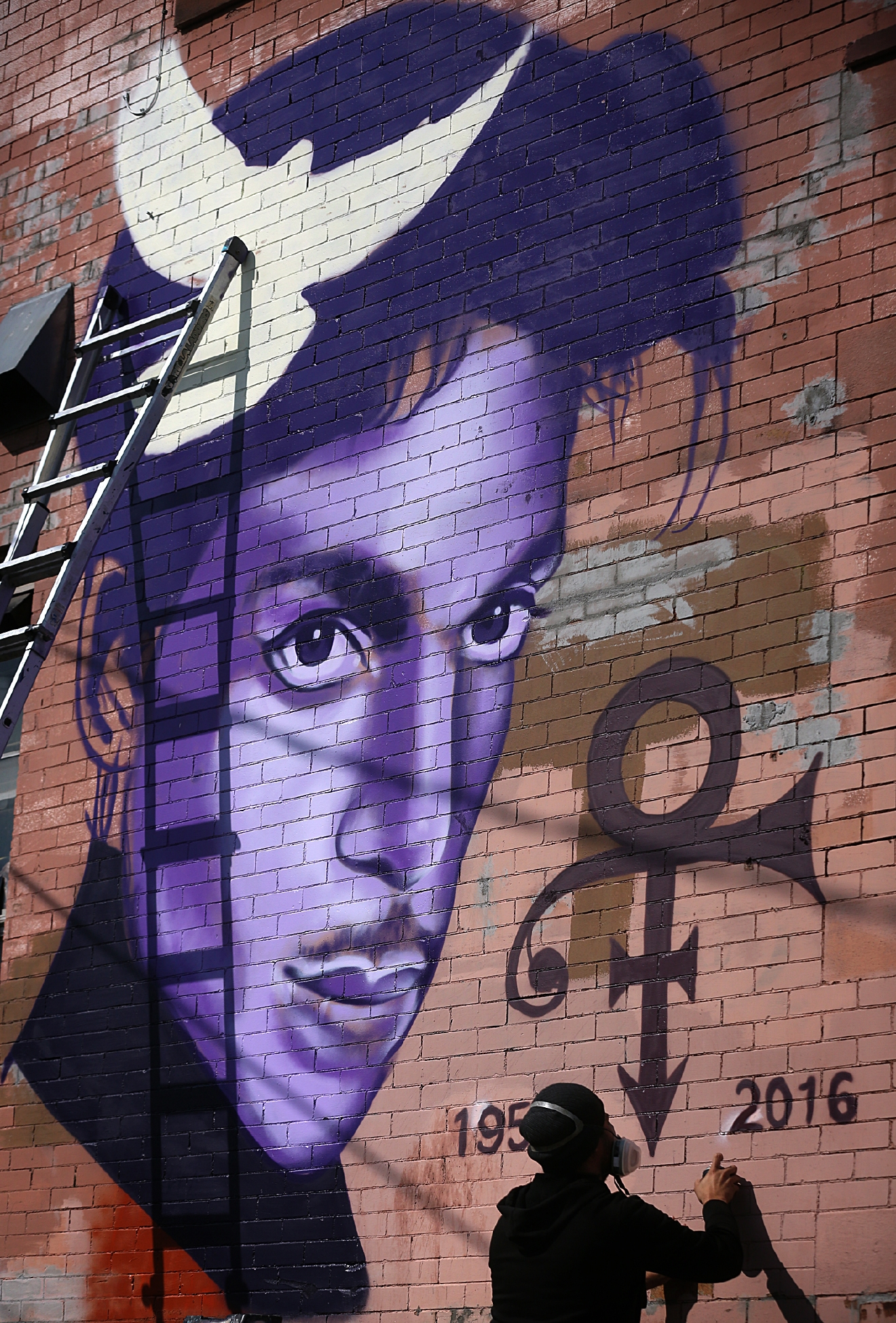 Artist Rock Martinez continues work on a mural he is painting of musician Prince in Minneapolis, Saturday, April 23, 2016. The pop superstar died Thursday at the age of 57. (Jim Gehrz /Star Tribune via AP)