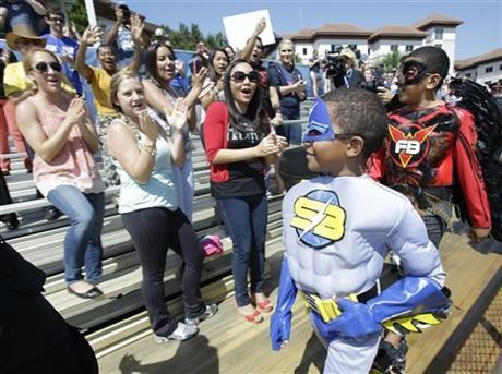 Supporters cheer for Jaylen Hyde, foreground, aka %u201CStriker Boy,%u201D as he makes his way to an awaiting helicopter after having disarmed an explosive device, Friday, June 6, 2014.