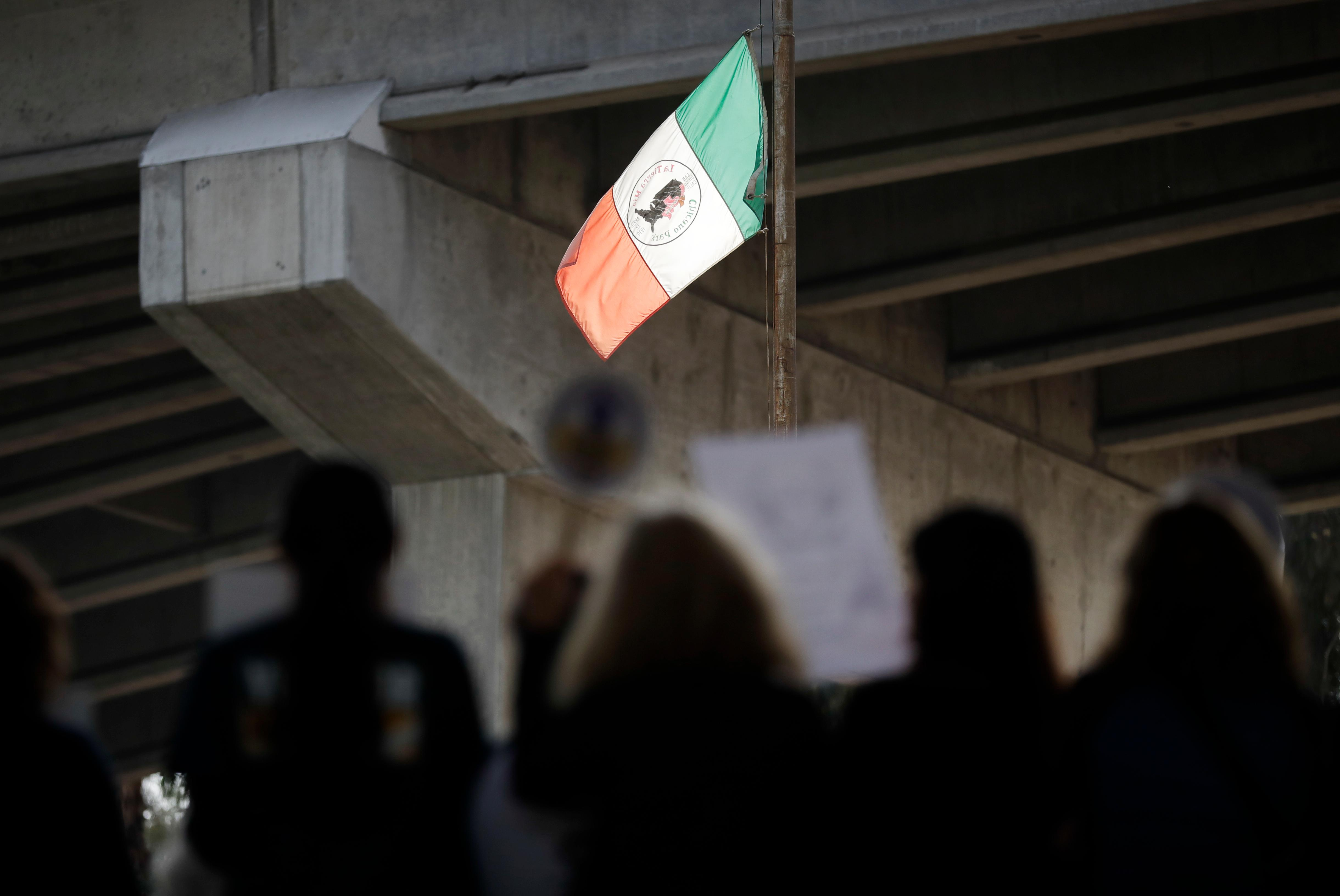 People attend a rally against a scheduled upcoming visit to the area by President Donald Trump as a flag fashioned after the flag of Mexico flies over Chicano Park Monday, March 12, 2018, in San Diego. Trump is scheduled to visit San Diego Tuesday, setting foot in California for his first time as president. (AP Photo/Gregory Bull)