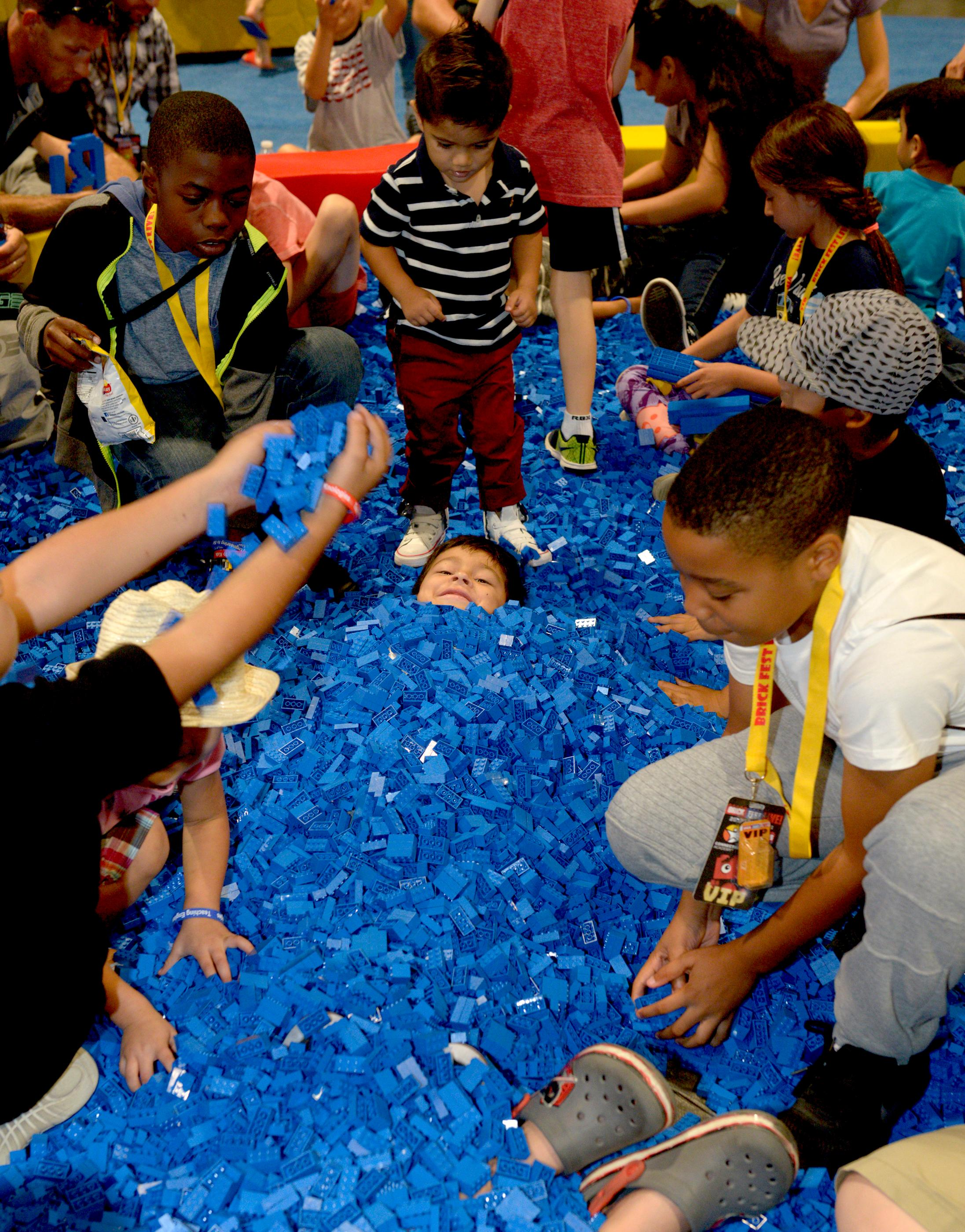 One young fan is buried up to his head in the Lego Sand Box during the Brick Fest Live Lego Fan Experience at the Las Vegas Convention Center, September 9, 2017. [Glenn Pinkerton/Las Vegas News Bureau]