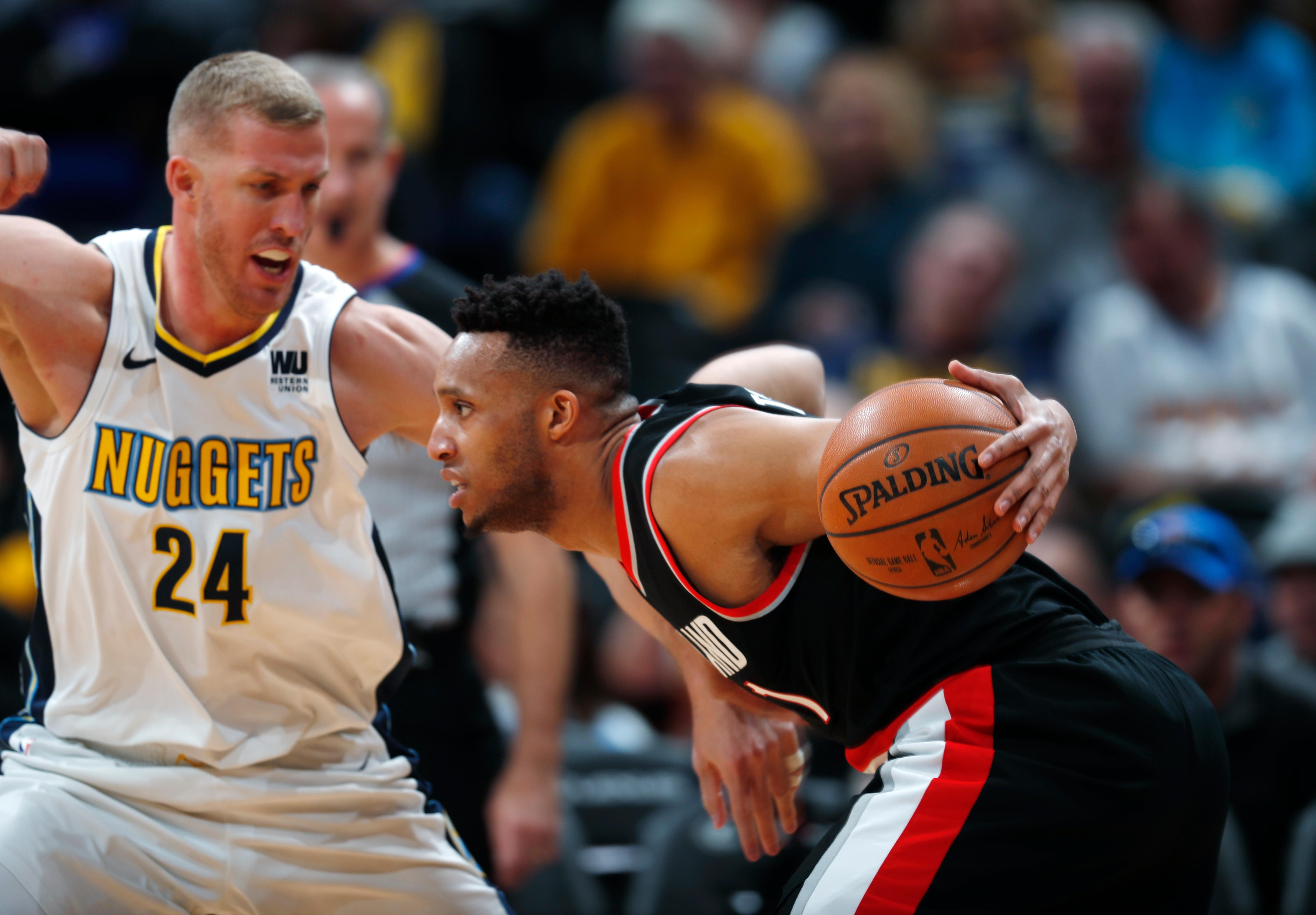 Denver Nuggets center Mason Plumlee, left, defends as Portland Trail Blazers guard Evan Turner tries to drive the lane in the first half of an NBA basketball game Monday, Jan. 22, 2018, in Denver. (AP Photo/David Zalubowski)