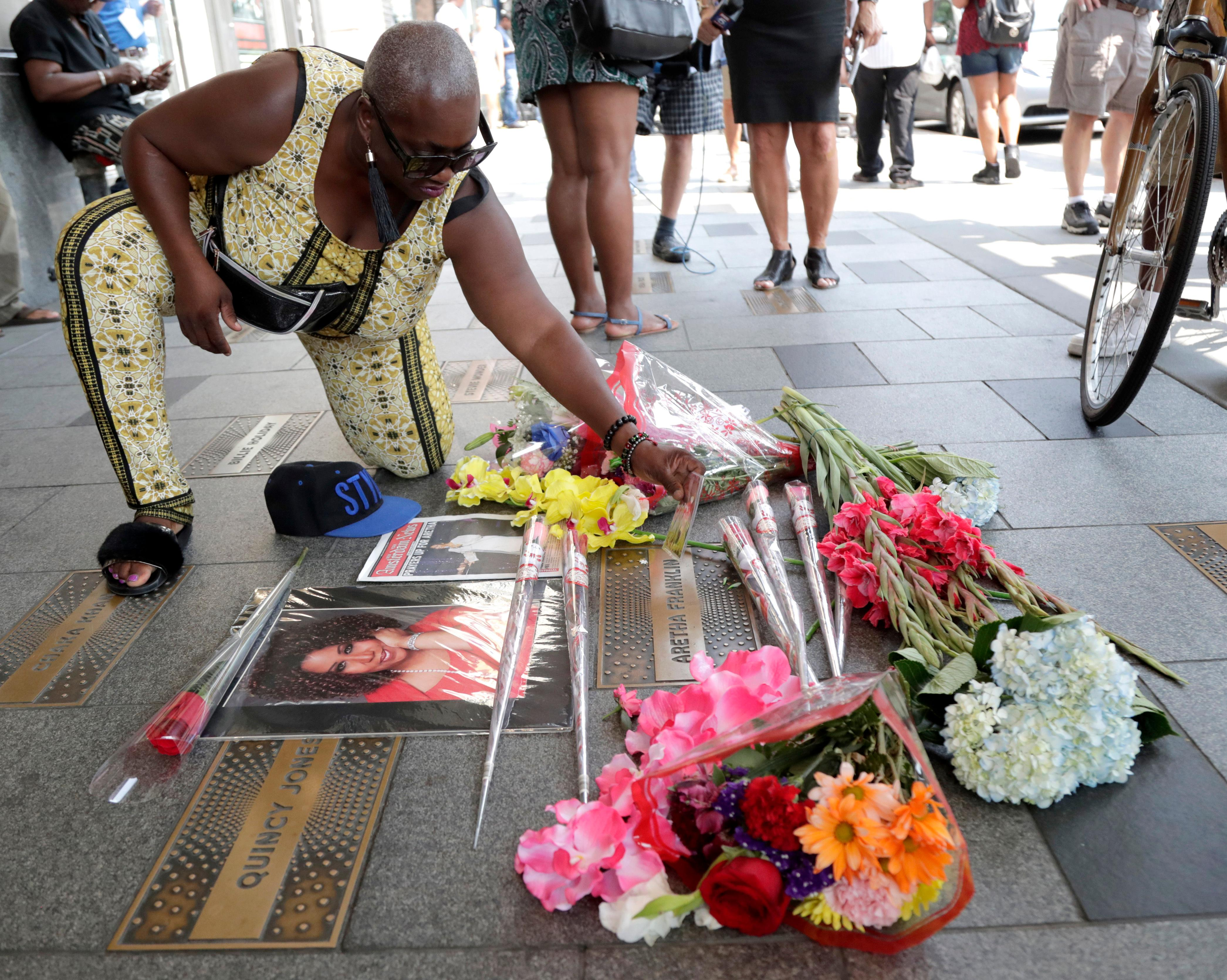 A woman arranges flowers and pictures on a makeshift memorial at the nameplate for singer Aretha Franklin outside the Apollo Theater in the Harlem section of New York, Thursday, Aug. 16, 2018. Franklin died Thursday at her home in Detroit at age 76. (AP Photo/Julio Cortez)