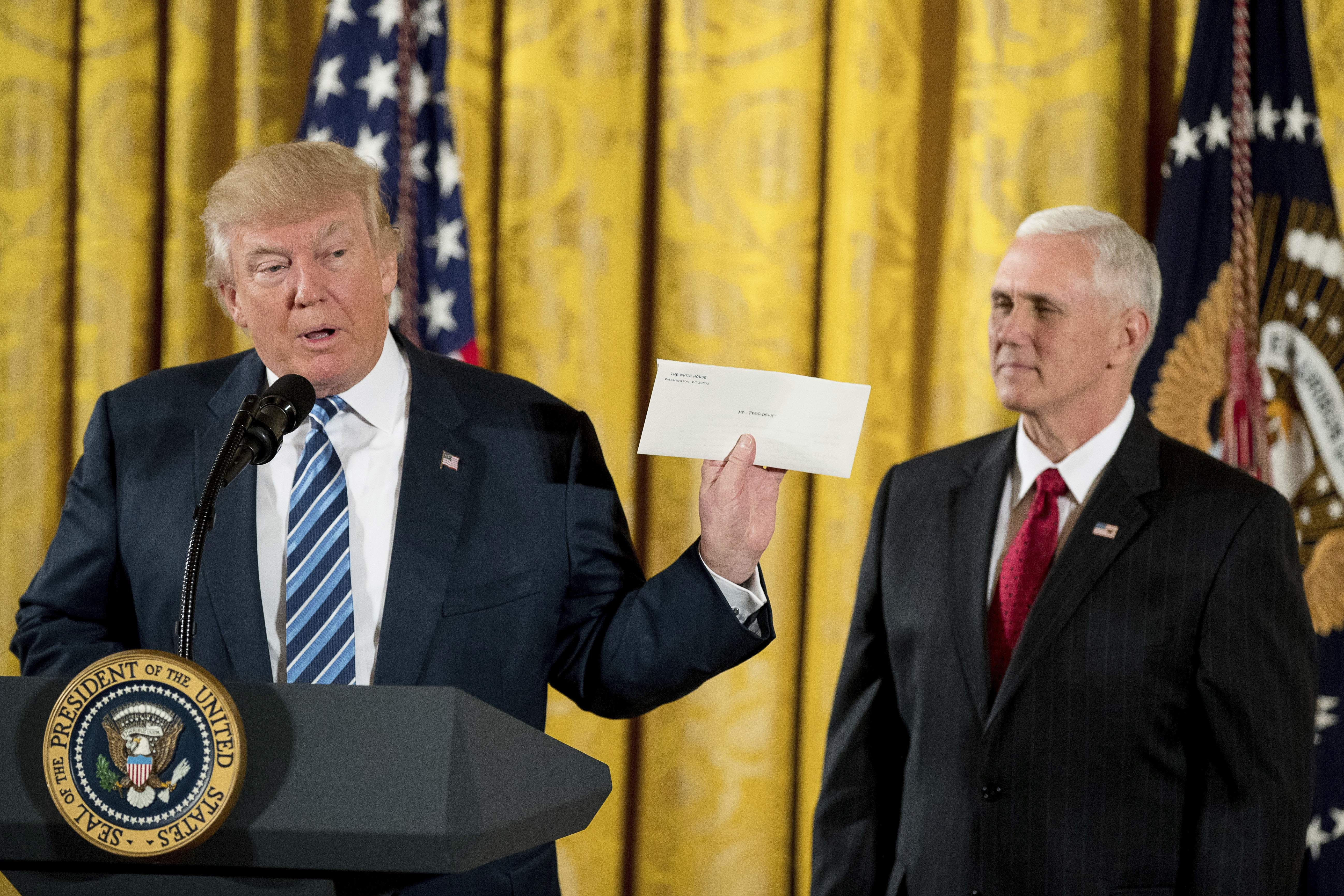 DAY 3 - In this Jan. 22, 2017, file photo, President Donald Trump, accompanied by Vice President Mike Pence, right, holds up a letter left for him by former President Barack Obama as he speaks at a White House senior staff swearing in ceremony in the East Room of the White House. (AP Photo/Andrew Harnik, file)