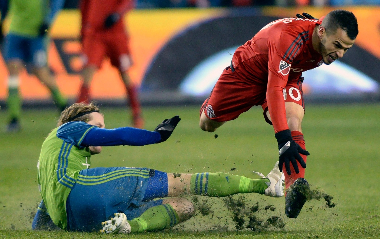 Seattle Sounders midfielder Erik Friberg, left, trips Toronto FC forward Sebastian Giovinco during first-half MLS Cup final soccer action in Toronto, Saturday, Dec. 10, 2016. (Nathan Denette/The Canadian Press via AP)